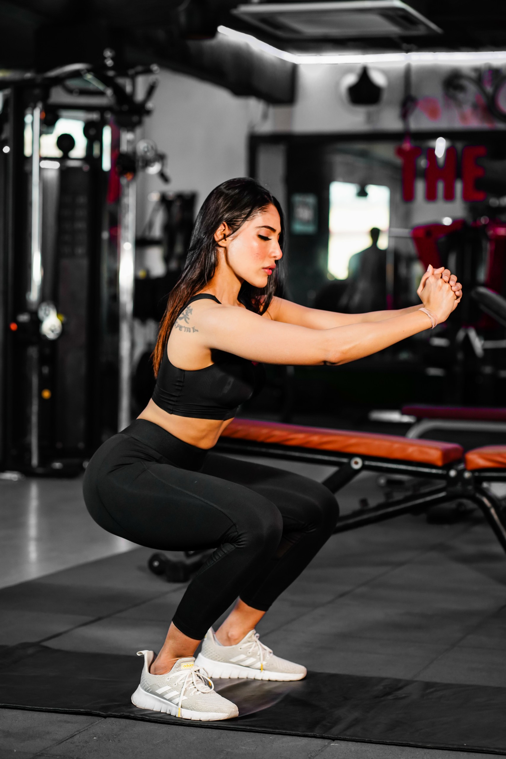 A girl squatting in the gym