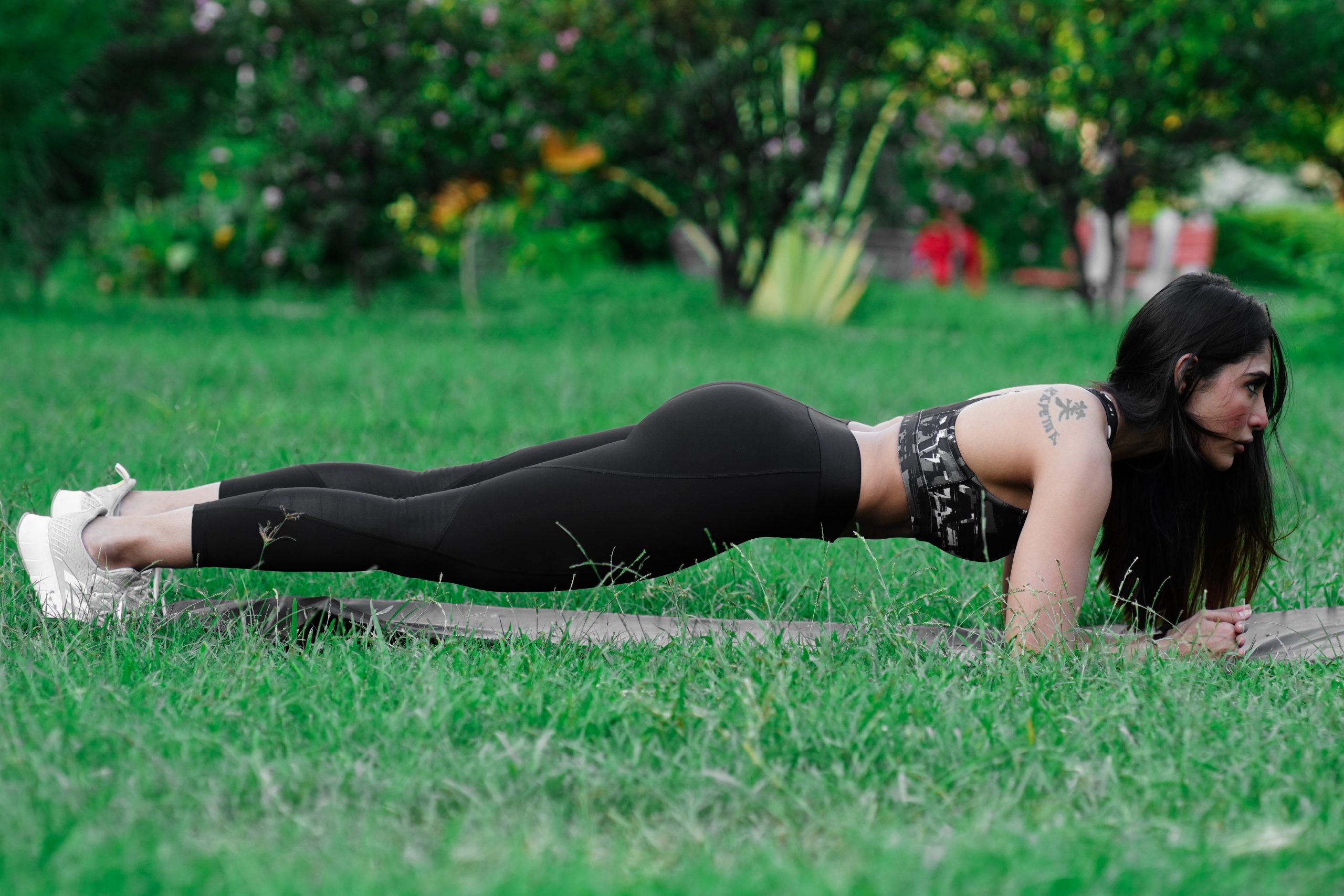 Athletic woman doing plank exercise outdoors