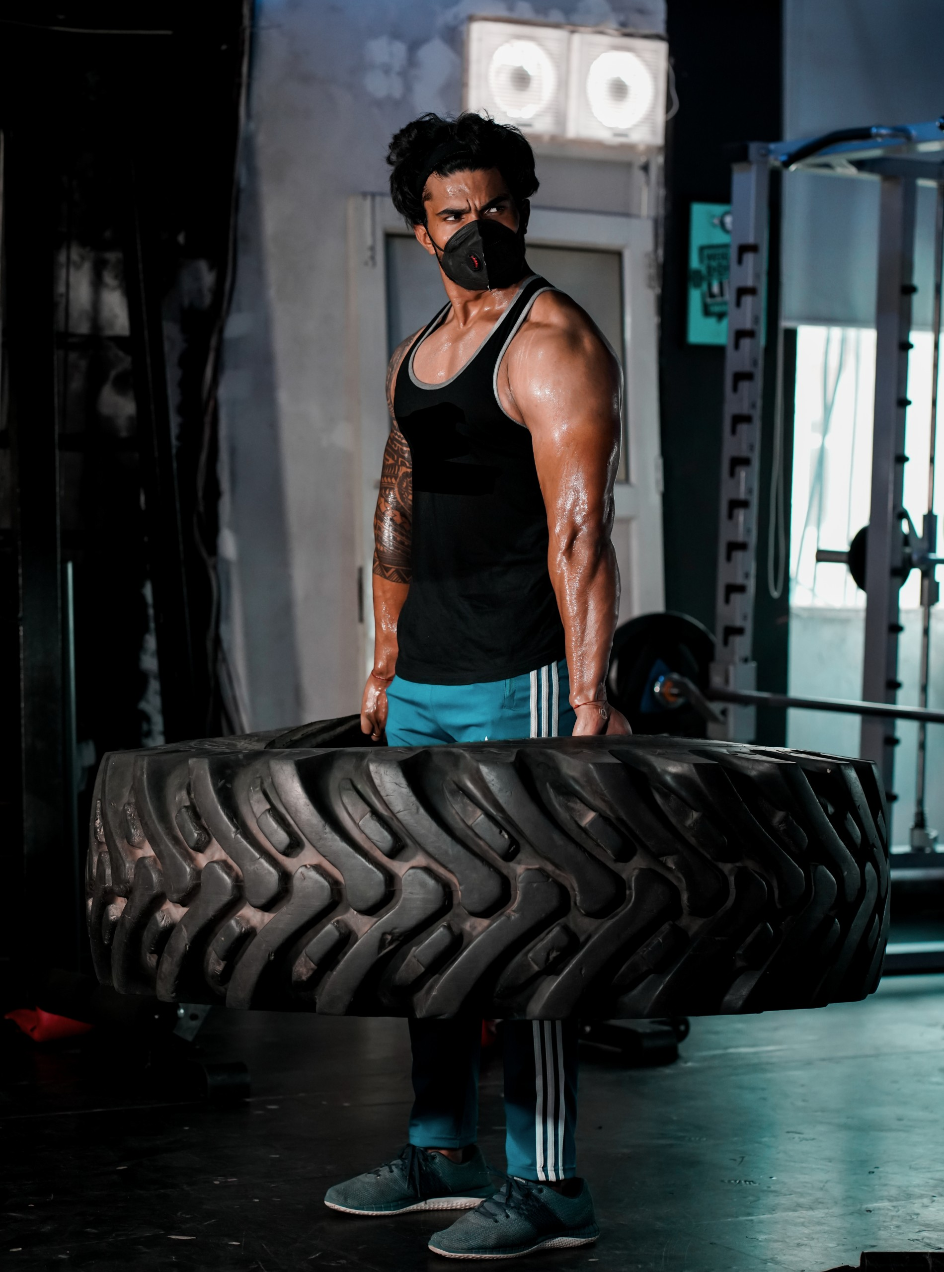Bodybuilder standing and lifting crossfit tyre