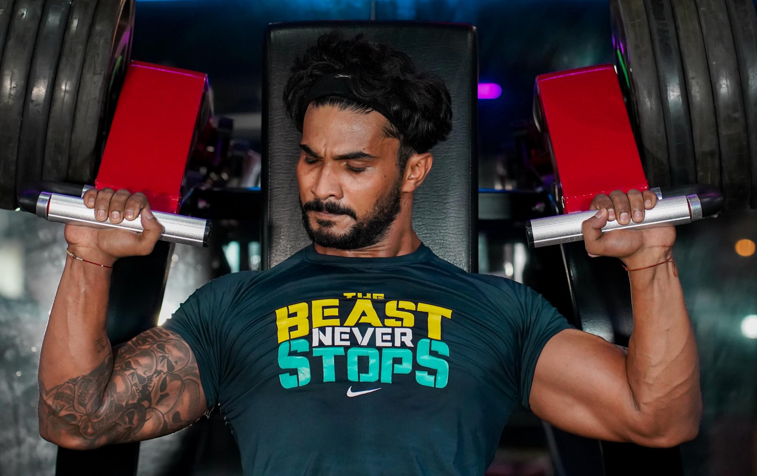 Boydbuilder at Shoulder PRess machine in gym
