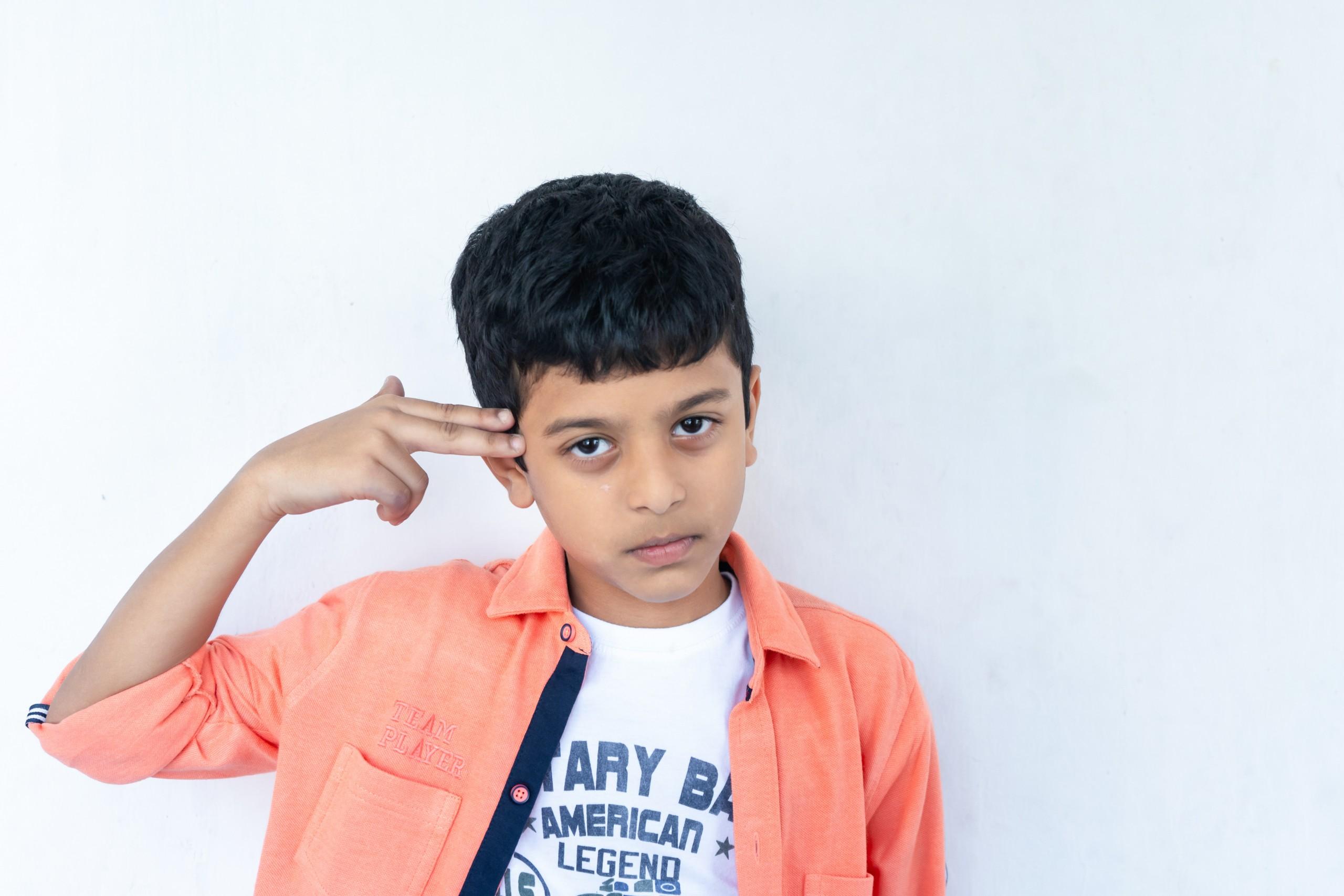 Boy holding a finger gun on his head