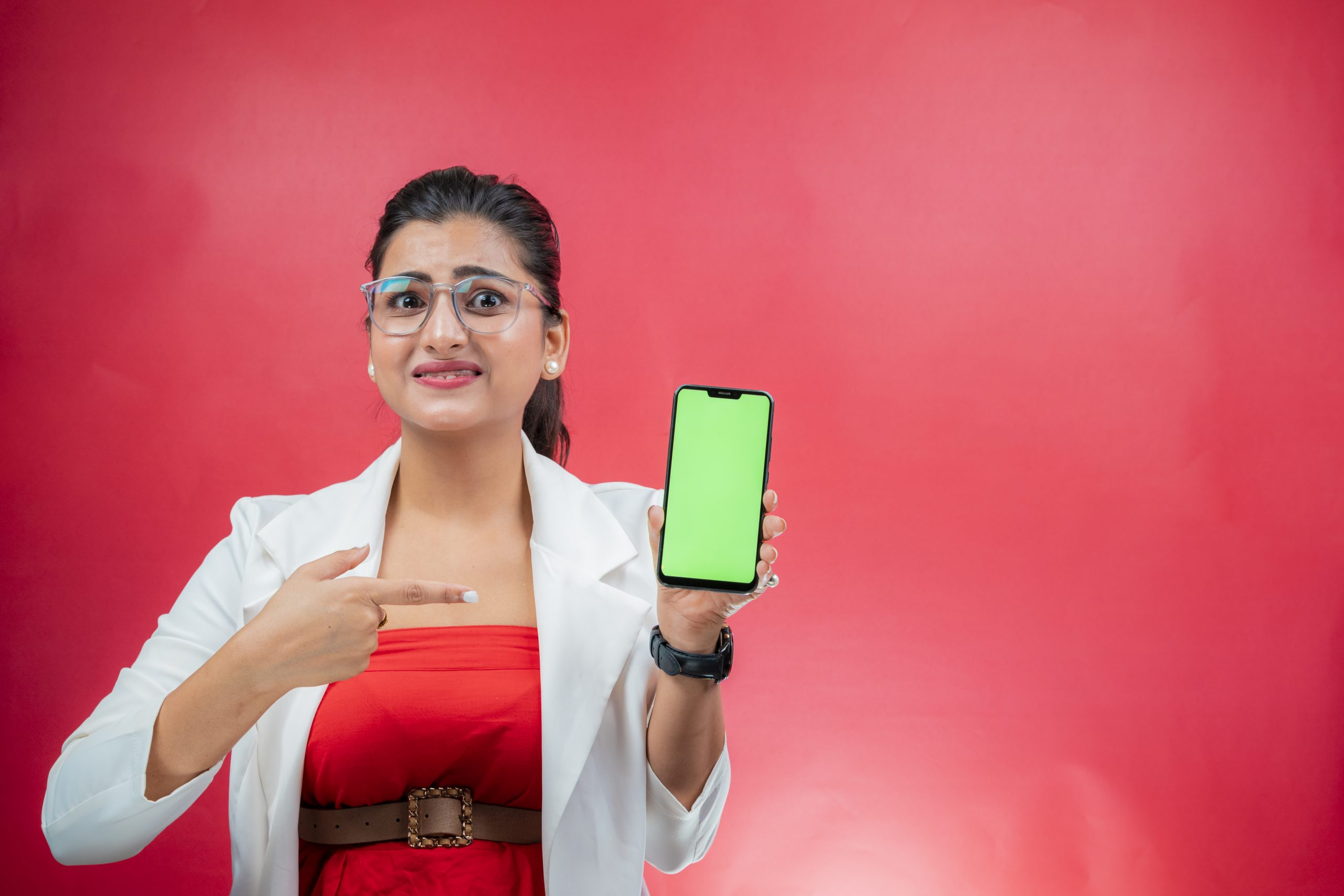 Disgruntled woman pointing towards green screen place holder phone