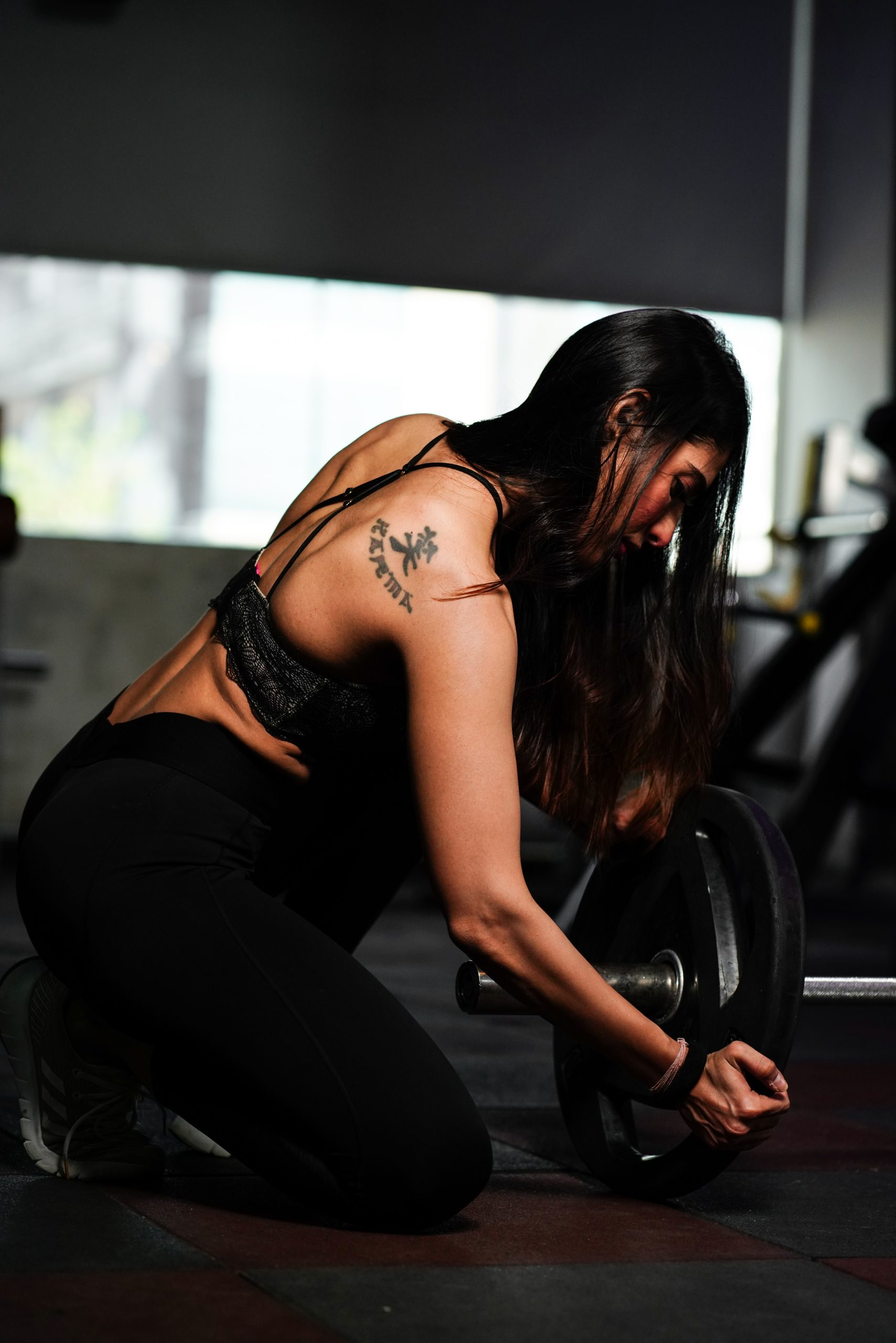 Female fitness model set the weights of a barbells
