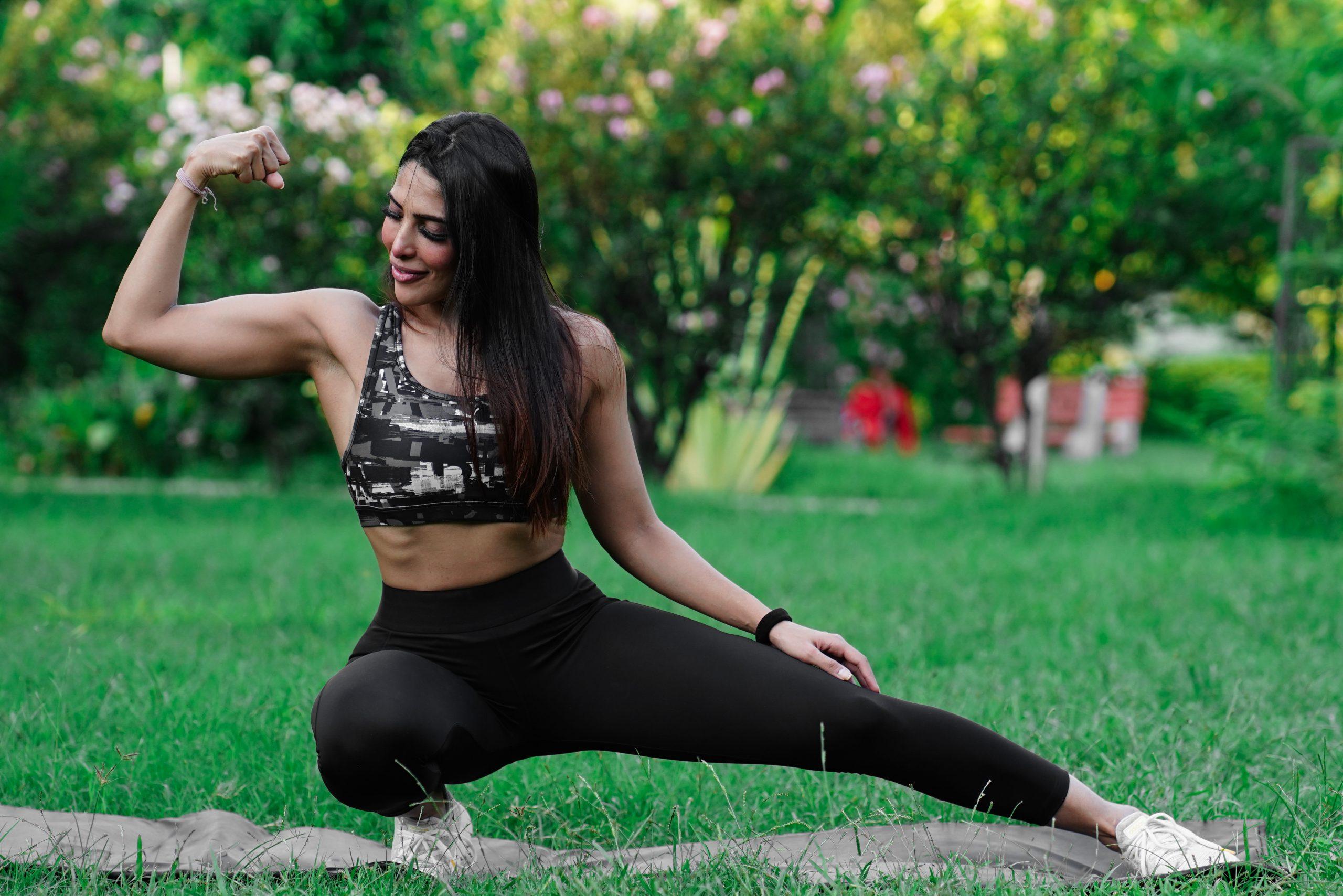 Female fitness model show her biceps in park