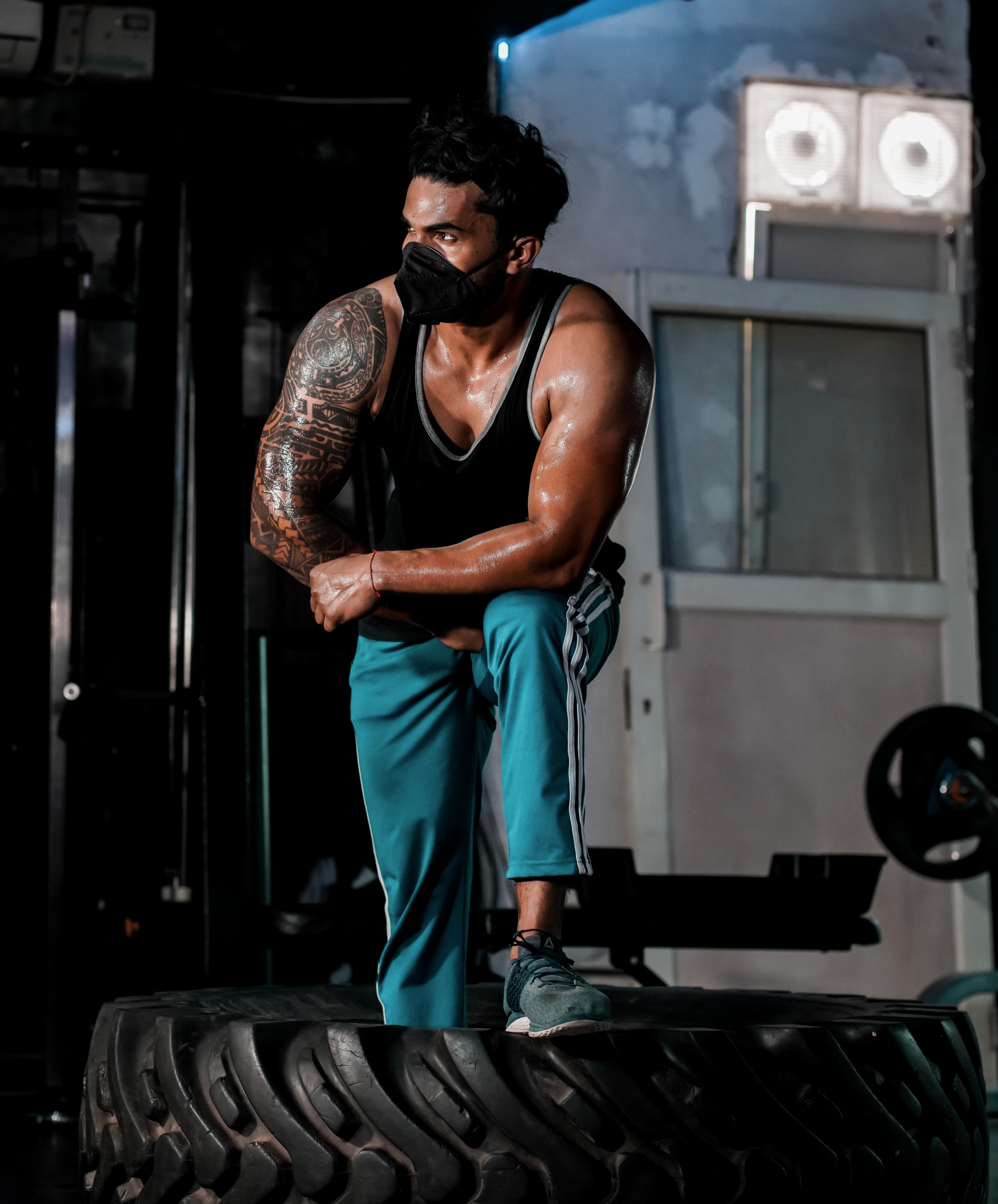 Fit Man Pose on Tire in the Gym