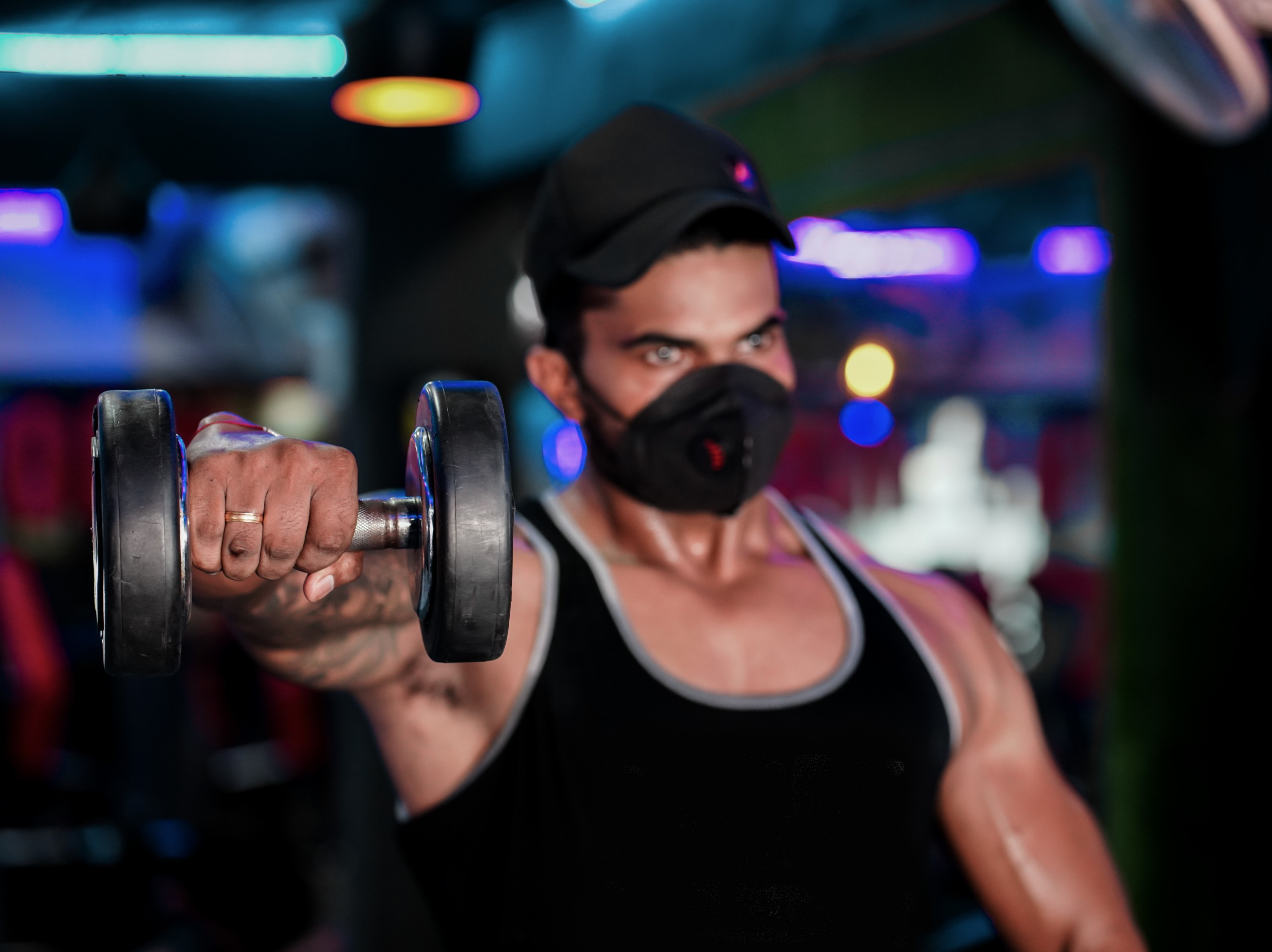Fit Man pushes dumbells in a Gym