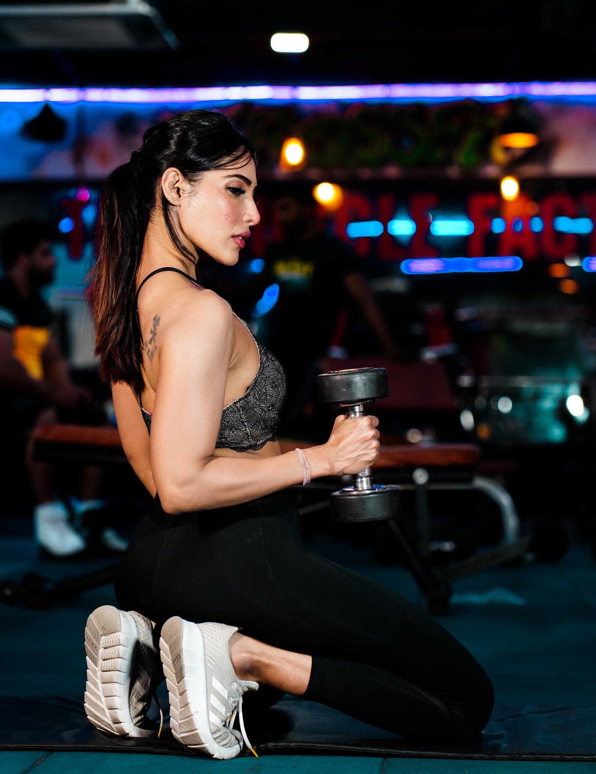 Fit Woman with dumbbells in the Gym