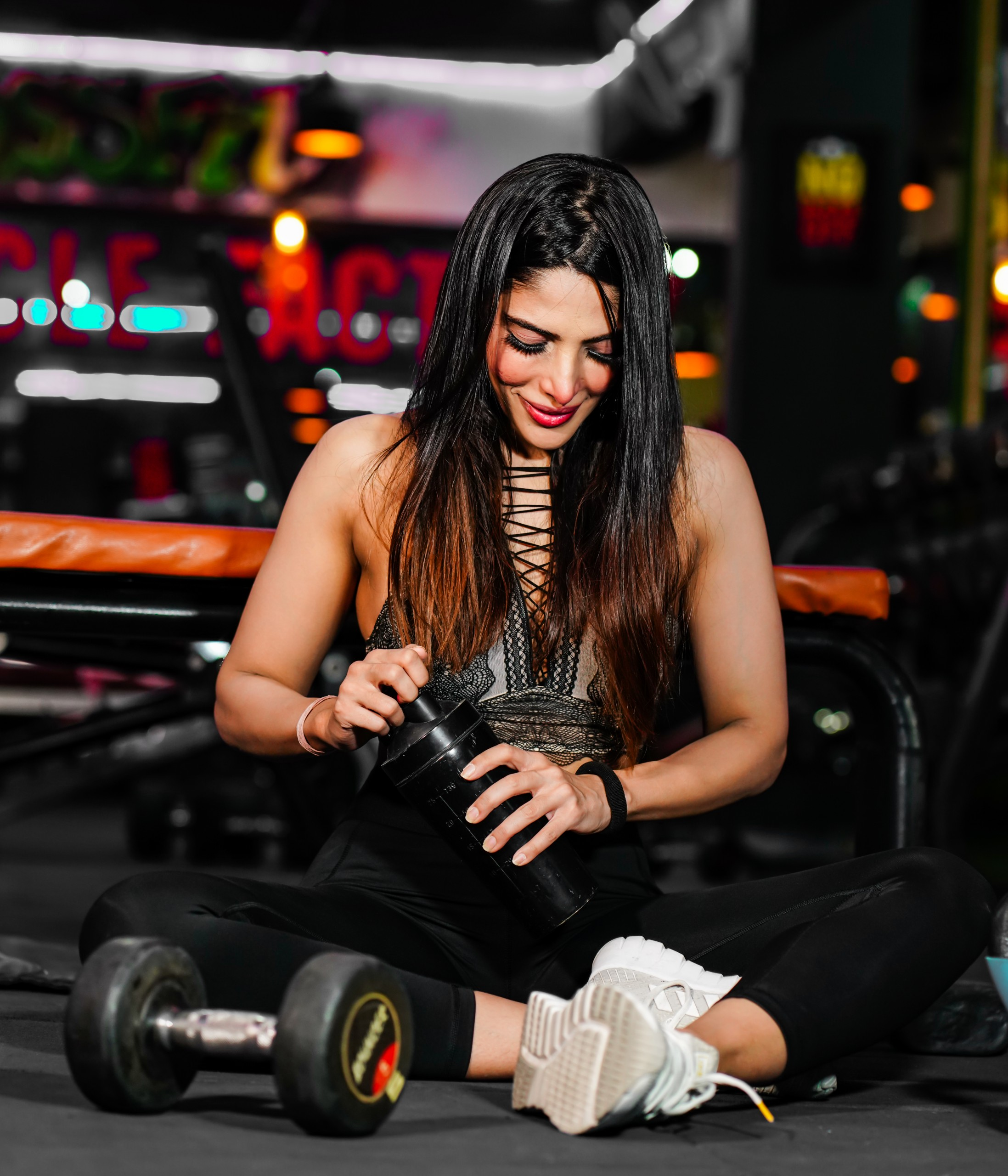 Fitness girl sitting on mat and relaxing after sports training in gym