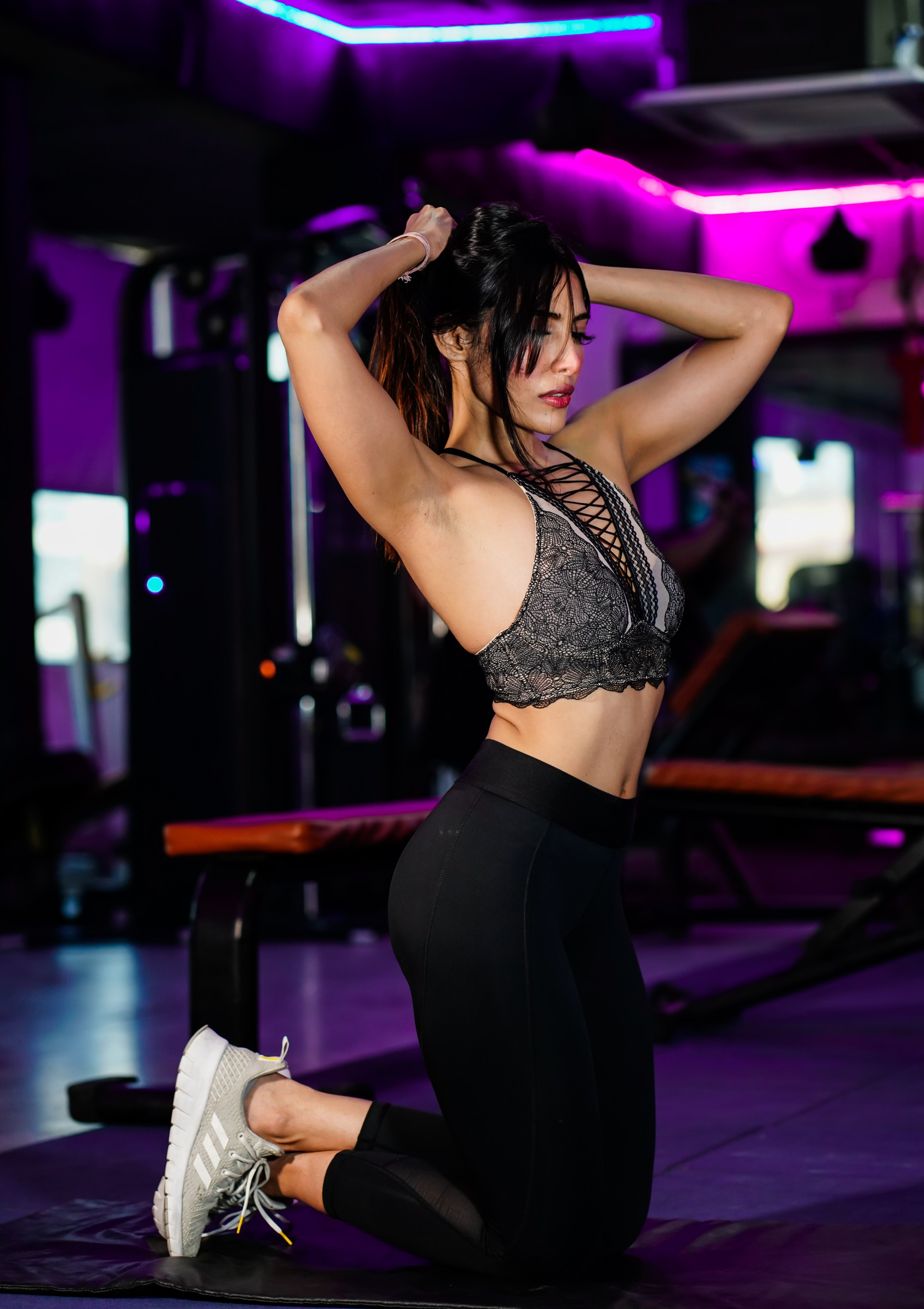 Fitness girl tie her hair in the gym