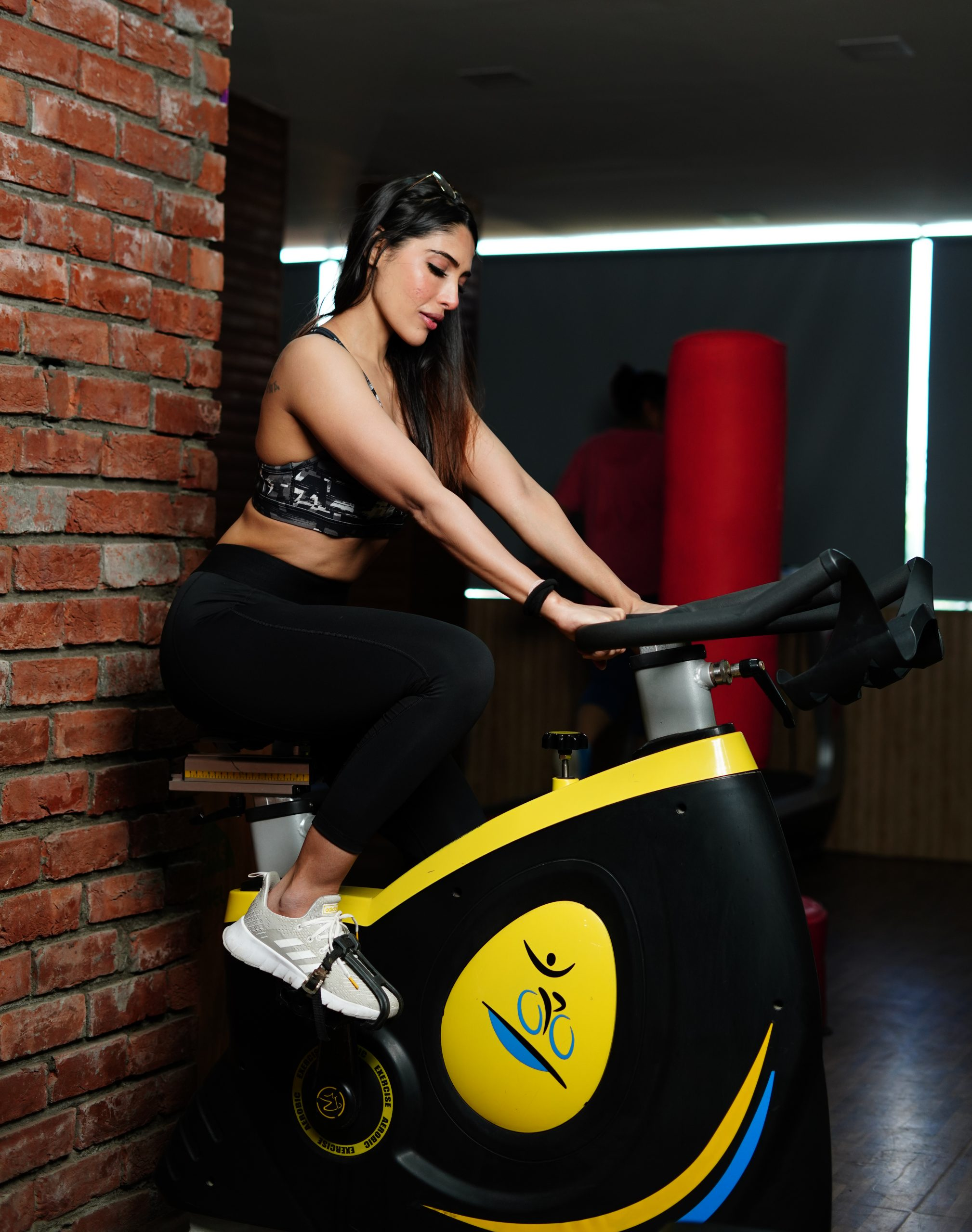 Fitness woman exercises on cycle in gym
