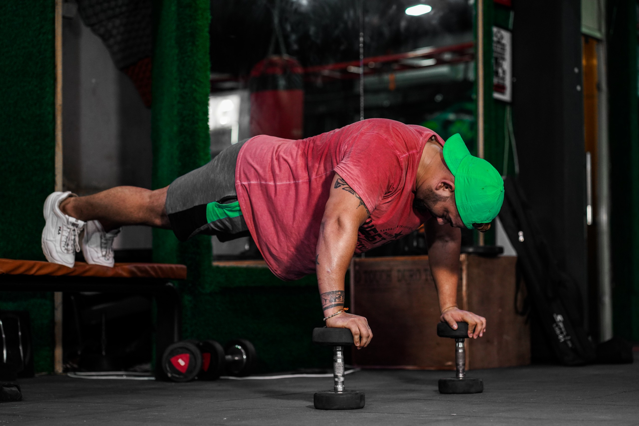 Gym man doing push-up exercise with dumbbell