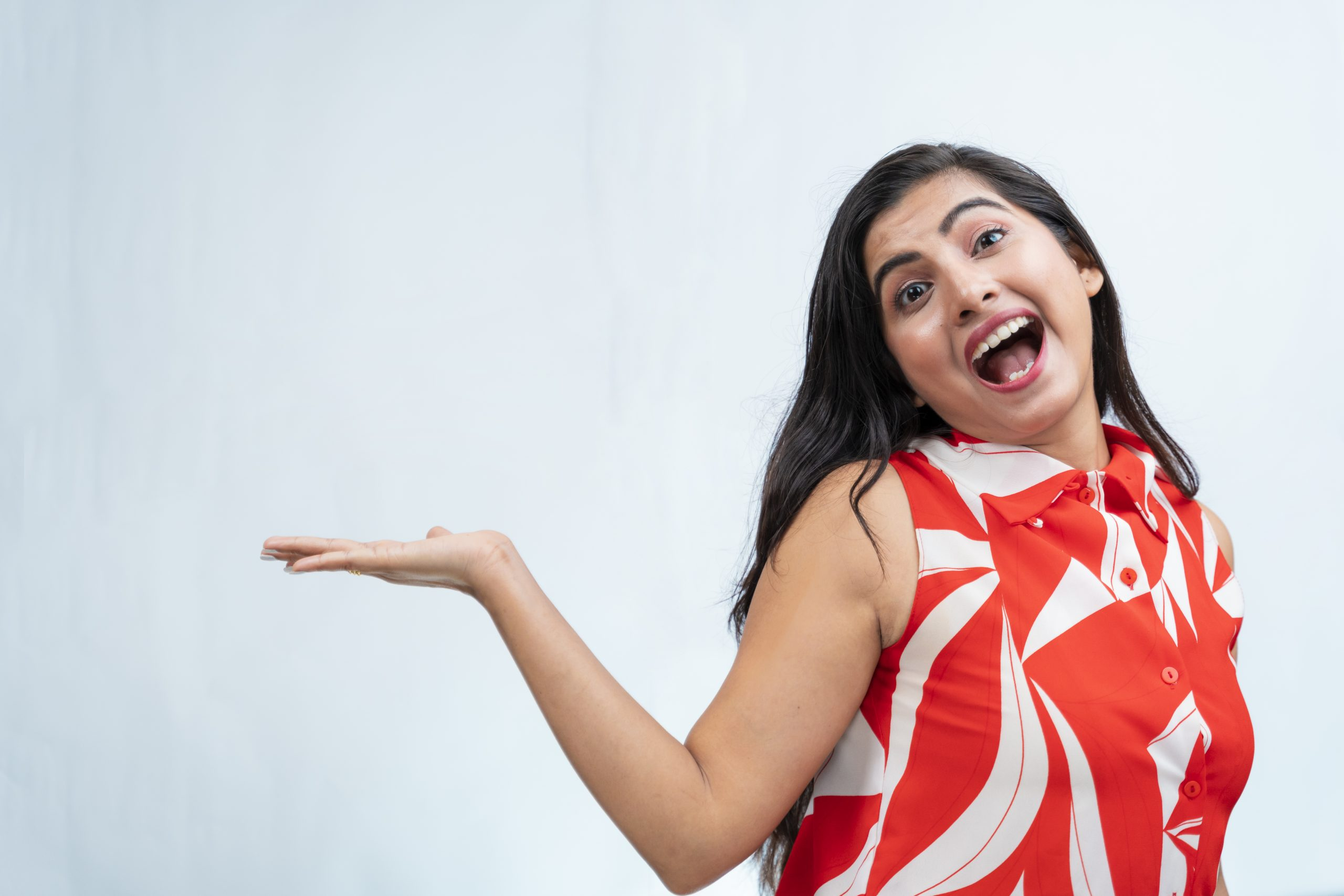 Happy indian girl pointing hand sideways
