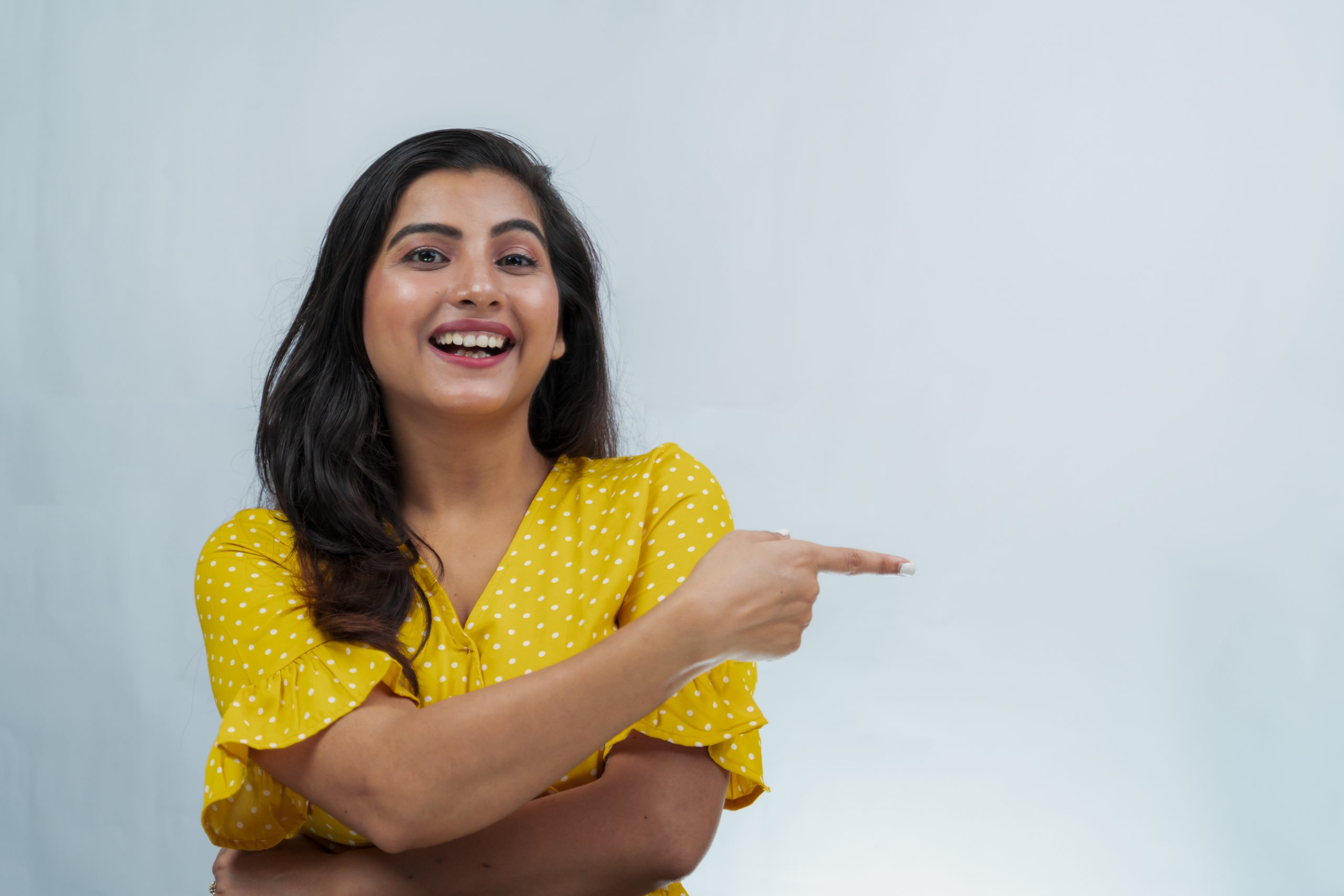 Happy young girl pointing sideways