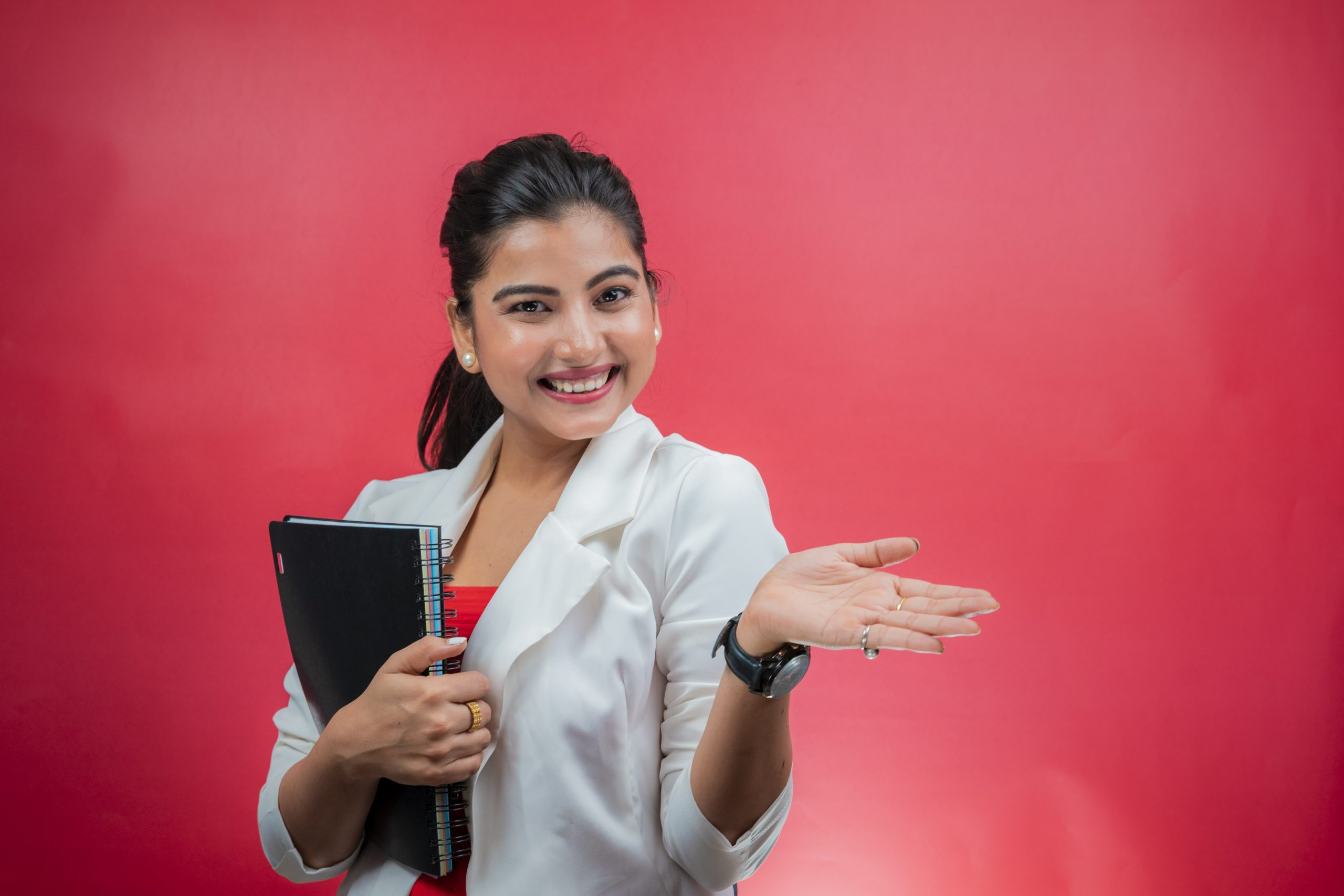 Happy young woman holding notebook and smiling with hand pointing sideways