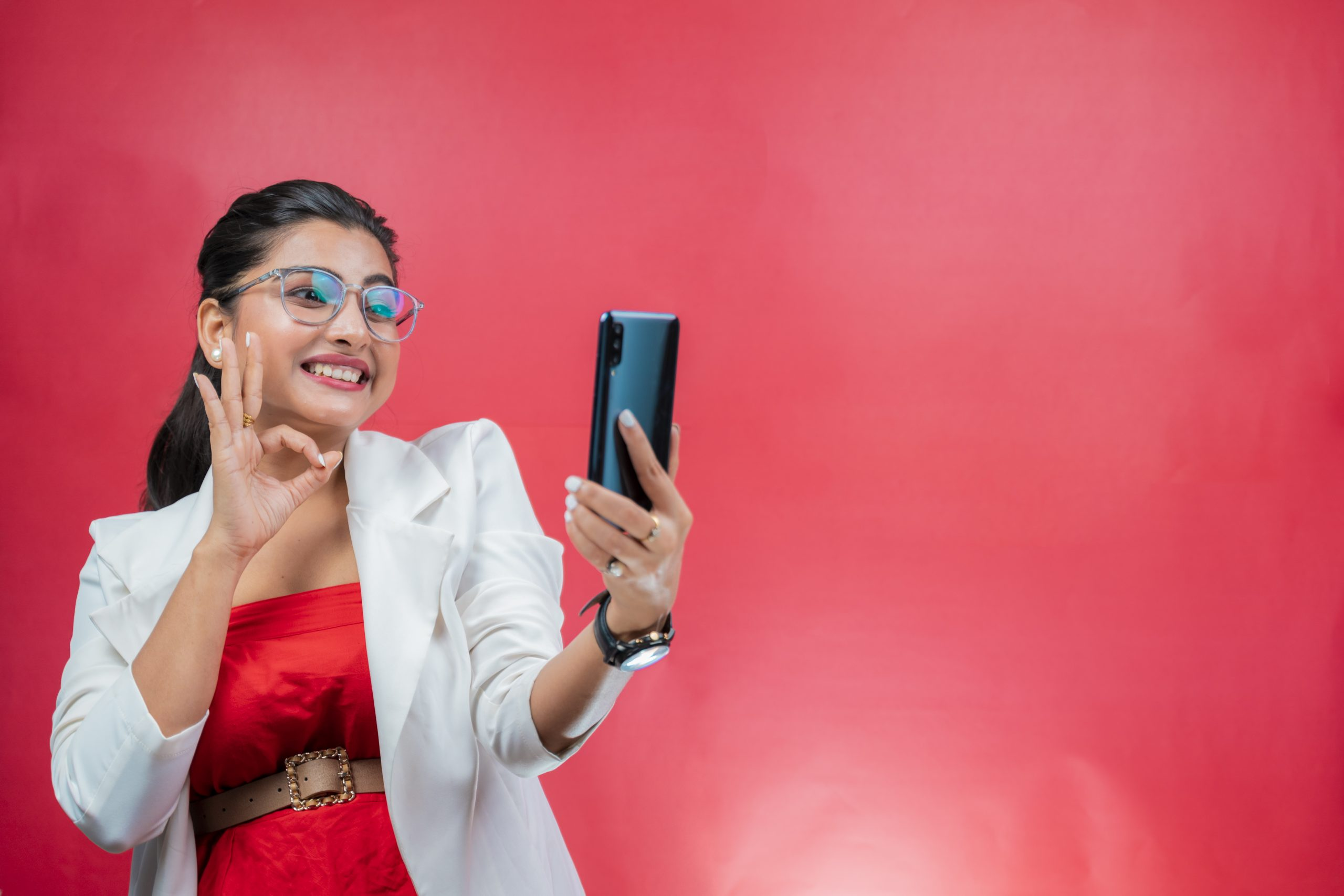 Happy young woman smiling and looking towards the phone and making OK gesture