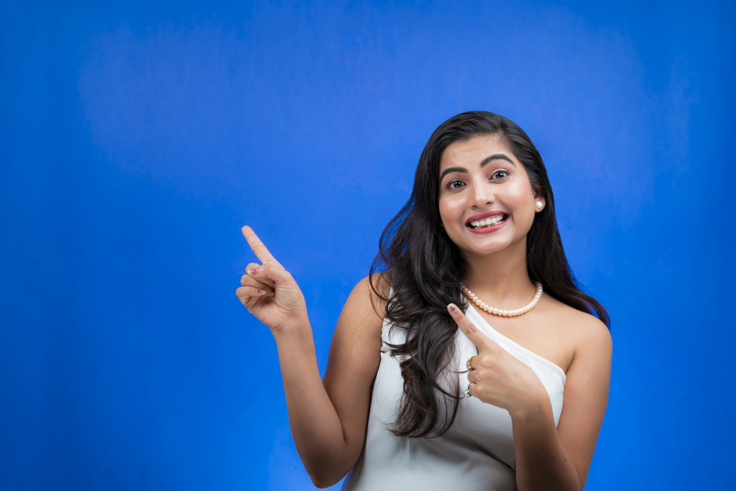 Happy young woman smiling and pointing sideways