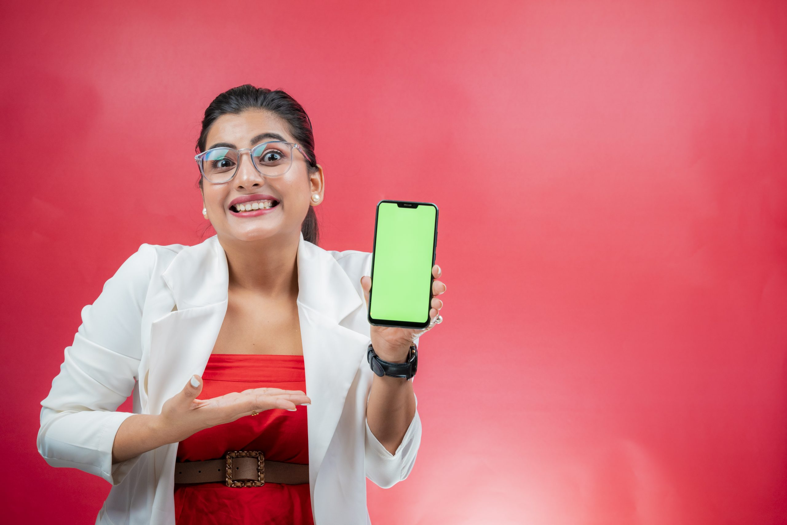 Happy young woman smiling and pointing towards green screen place holder phone