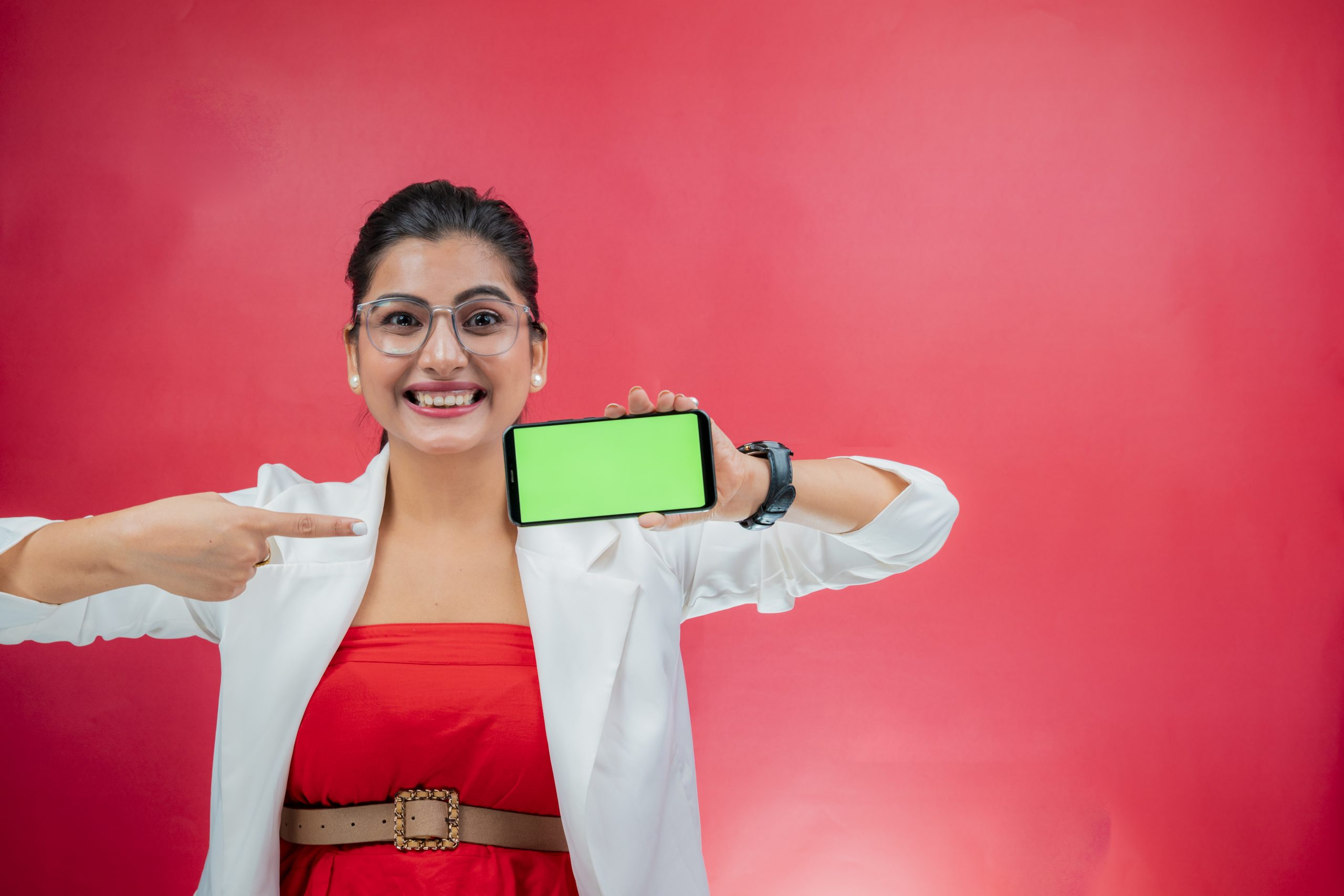 Happy young woman smiling and pointing towards green screen place holder phone horizontally