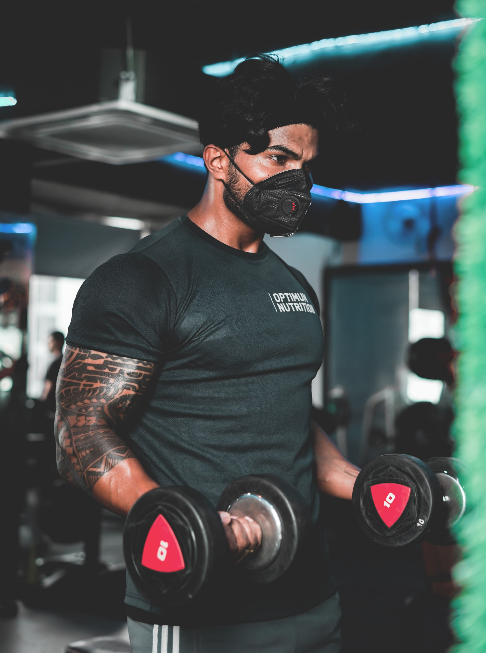 Man working out in a gym with a mask on