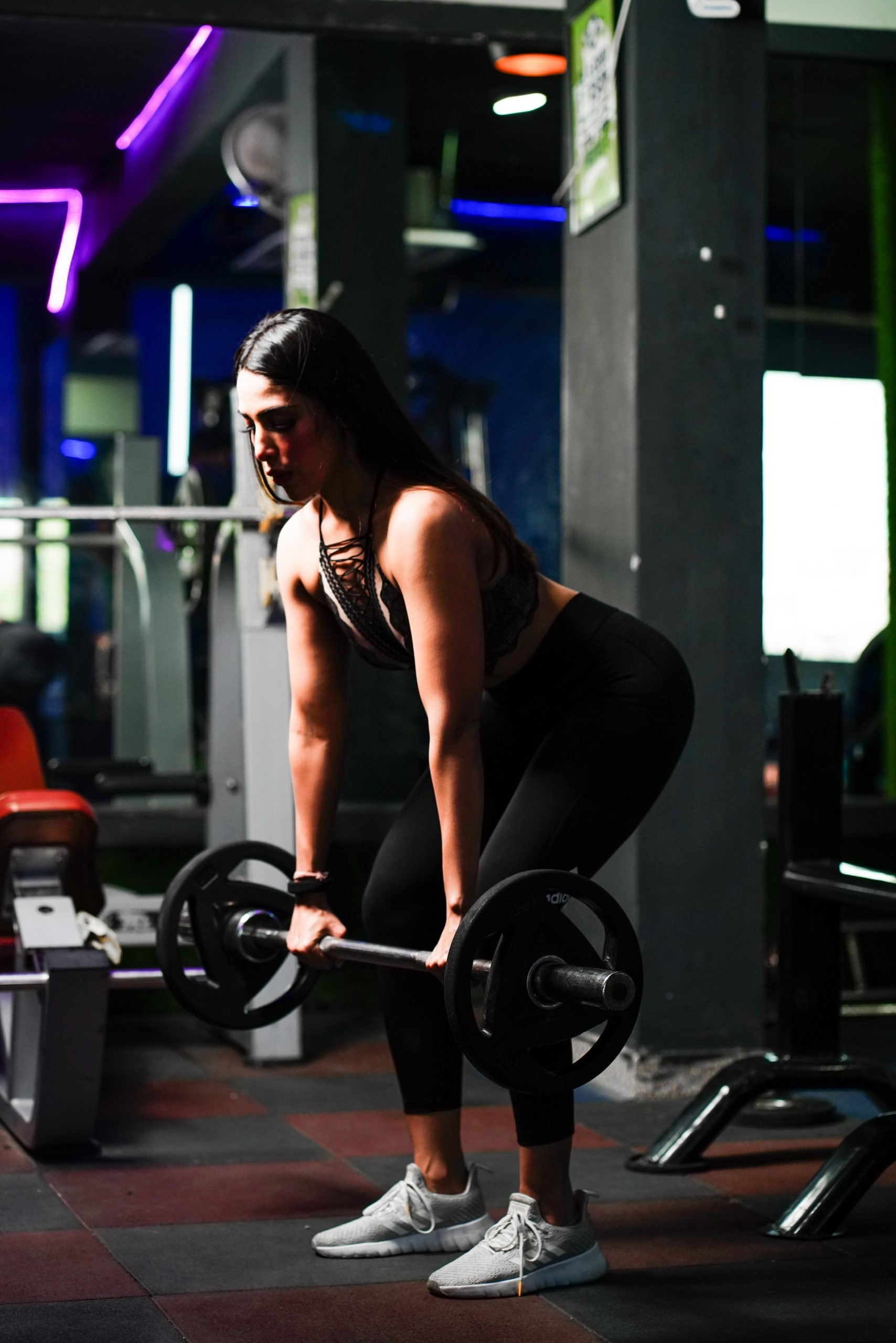 Muscles Woman exercising with barbell in gym