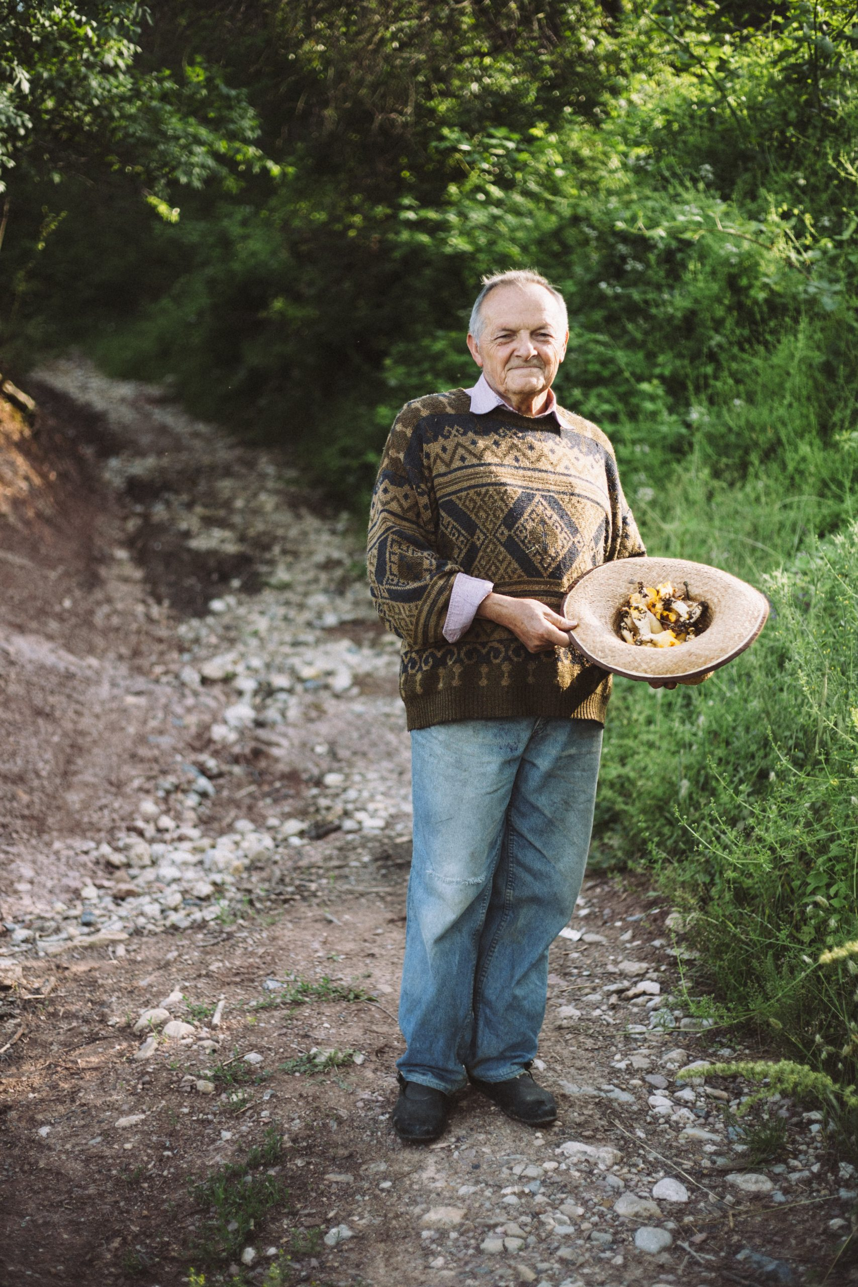 man collecting mushrooms in his hat