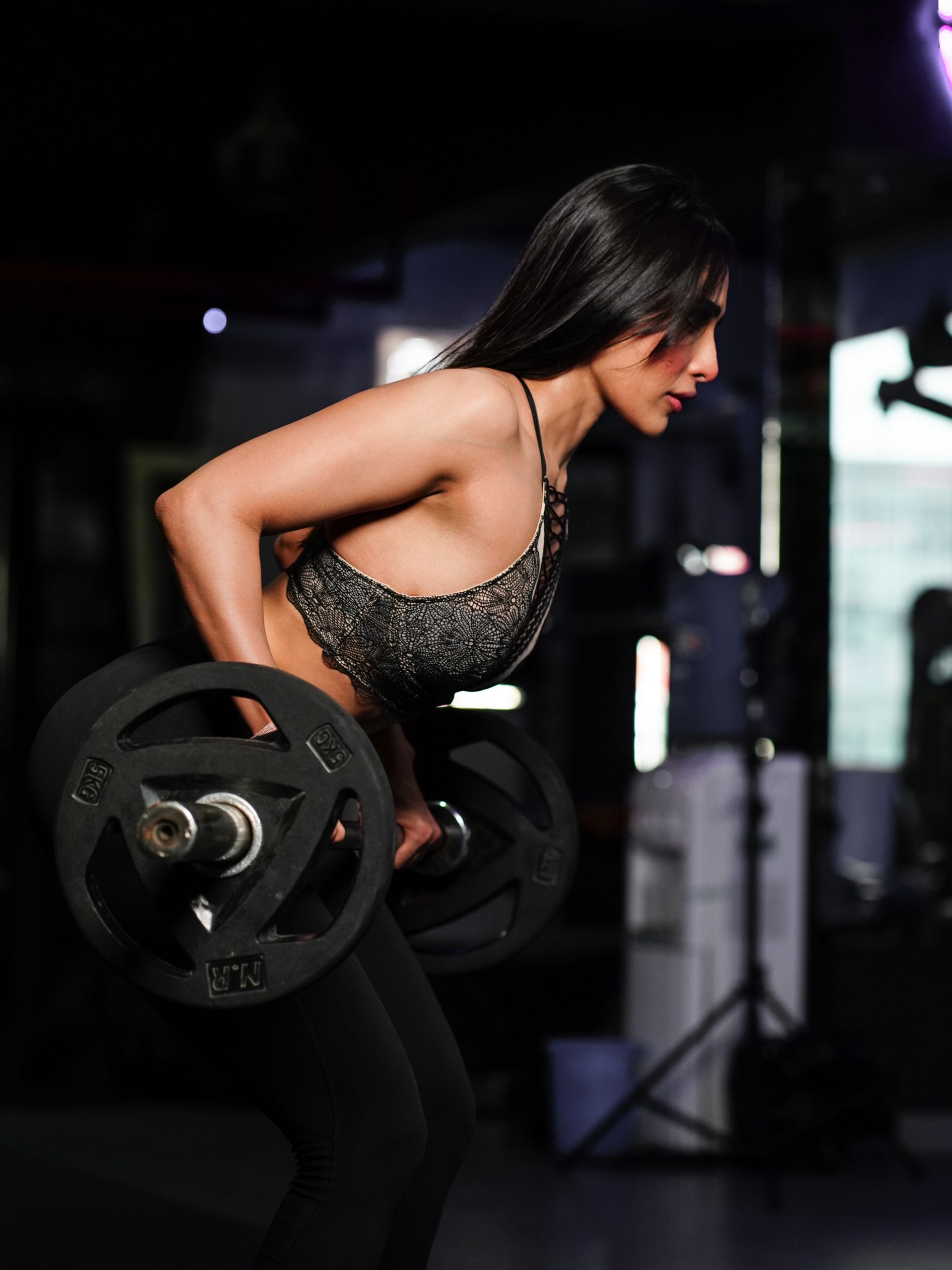Portrait of strong young woman lifting barbell during workout in modern gym