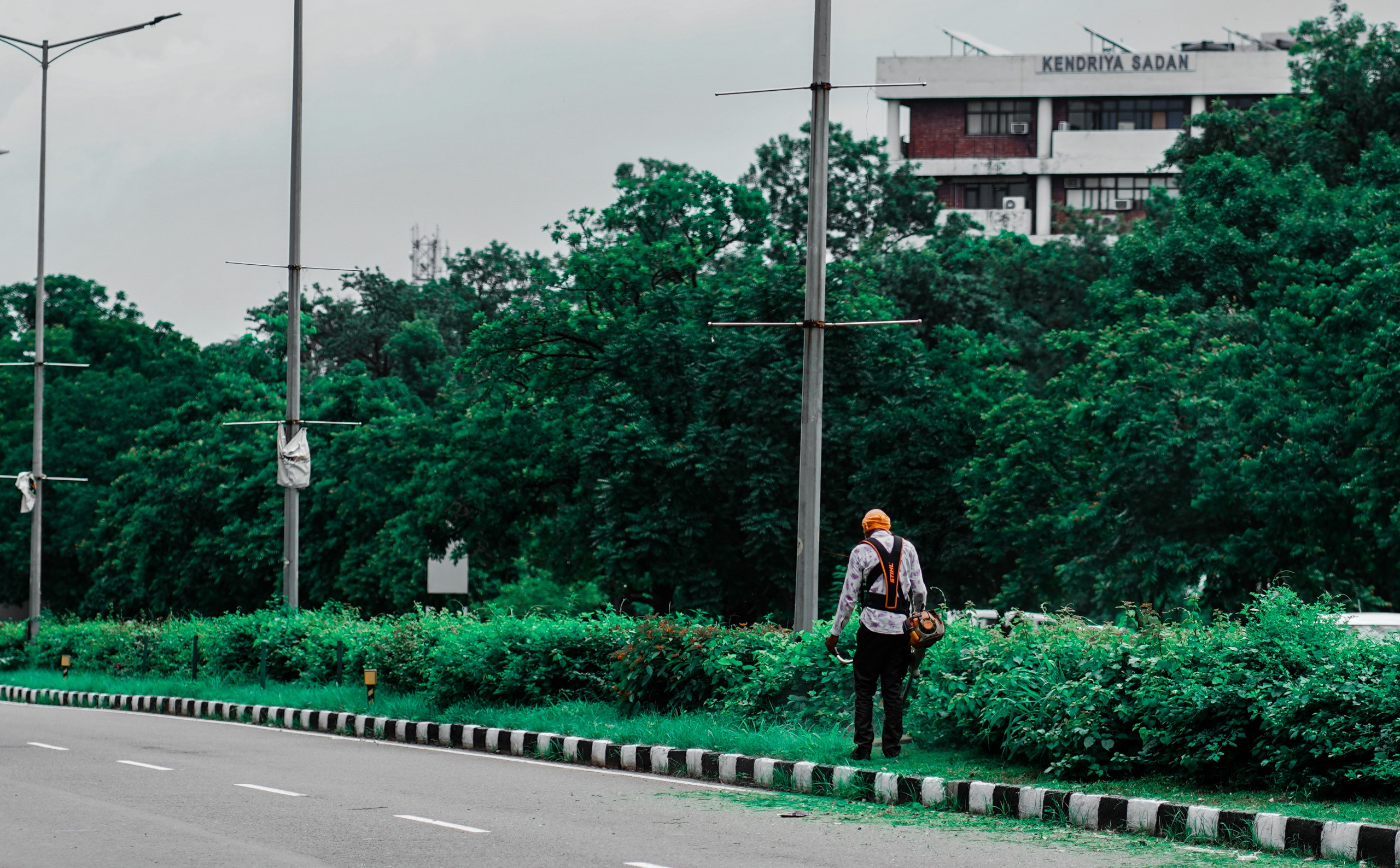 Road landscaper cutting grass along the highway using string lawn trimmer