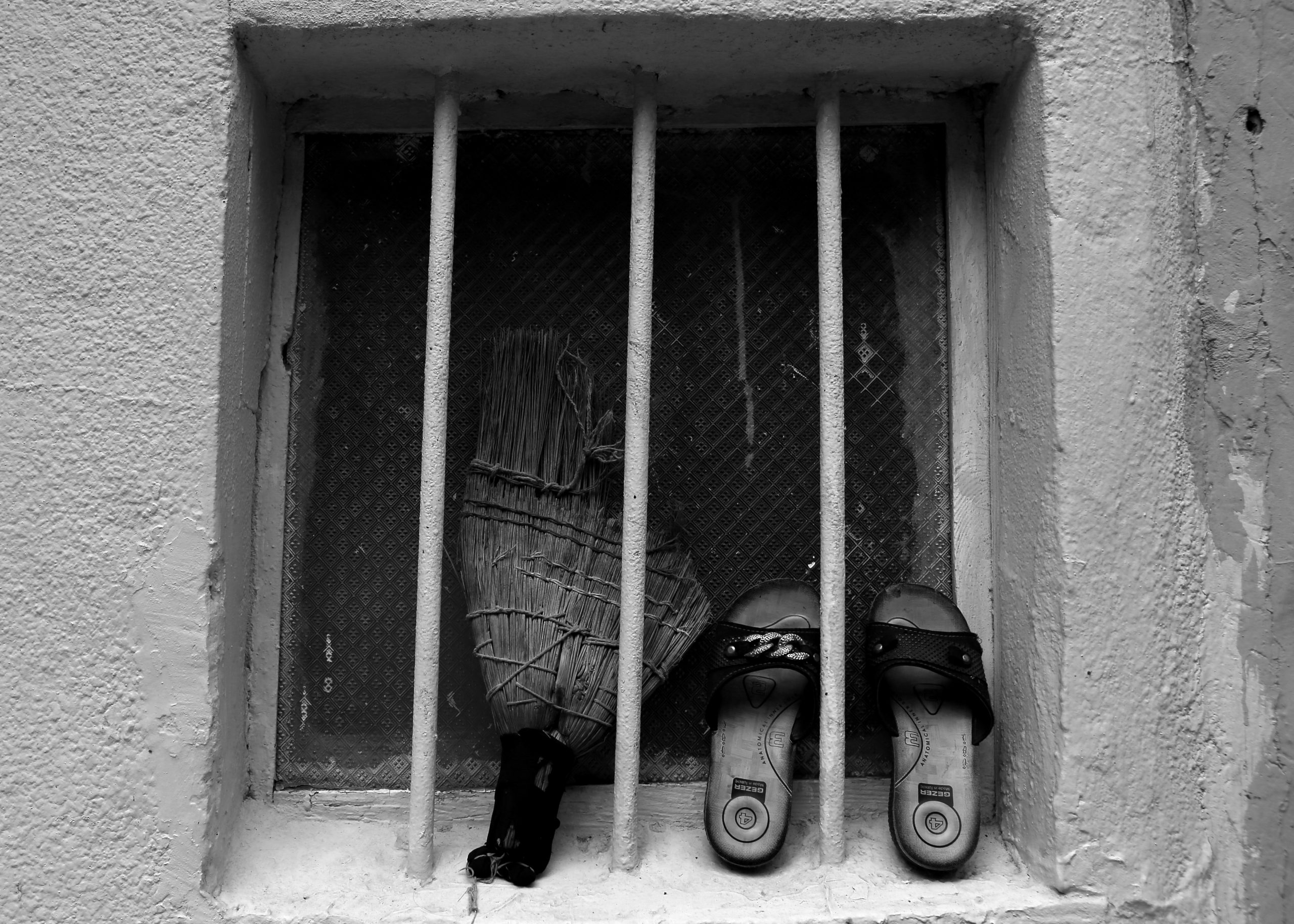 Slippers and broom in front of the window