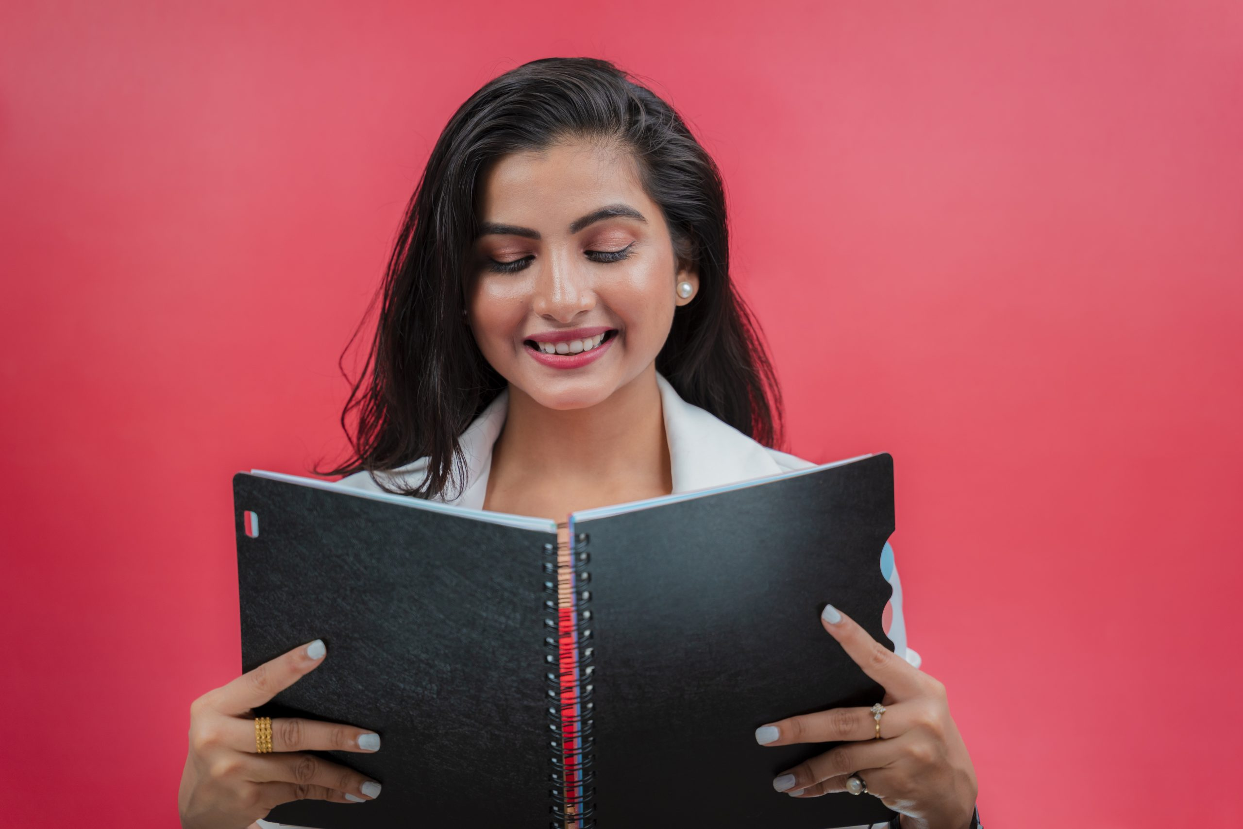 Smiling young woman reading book