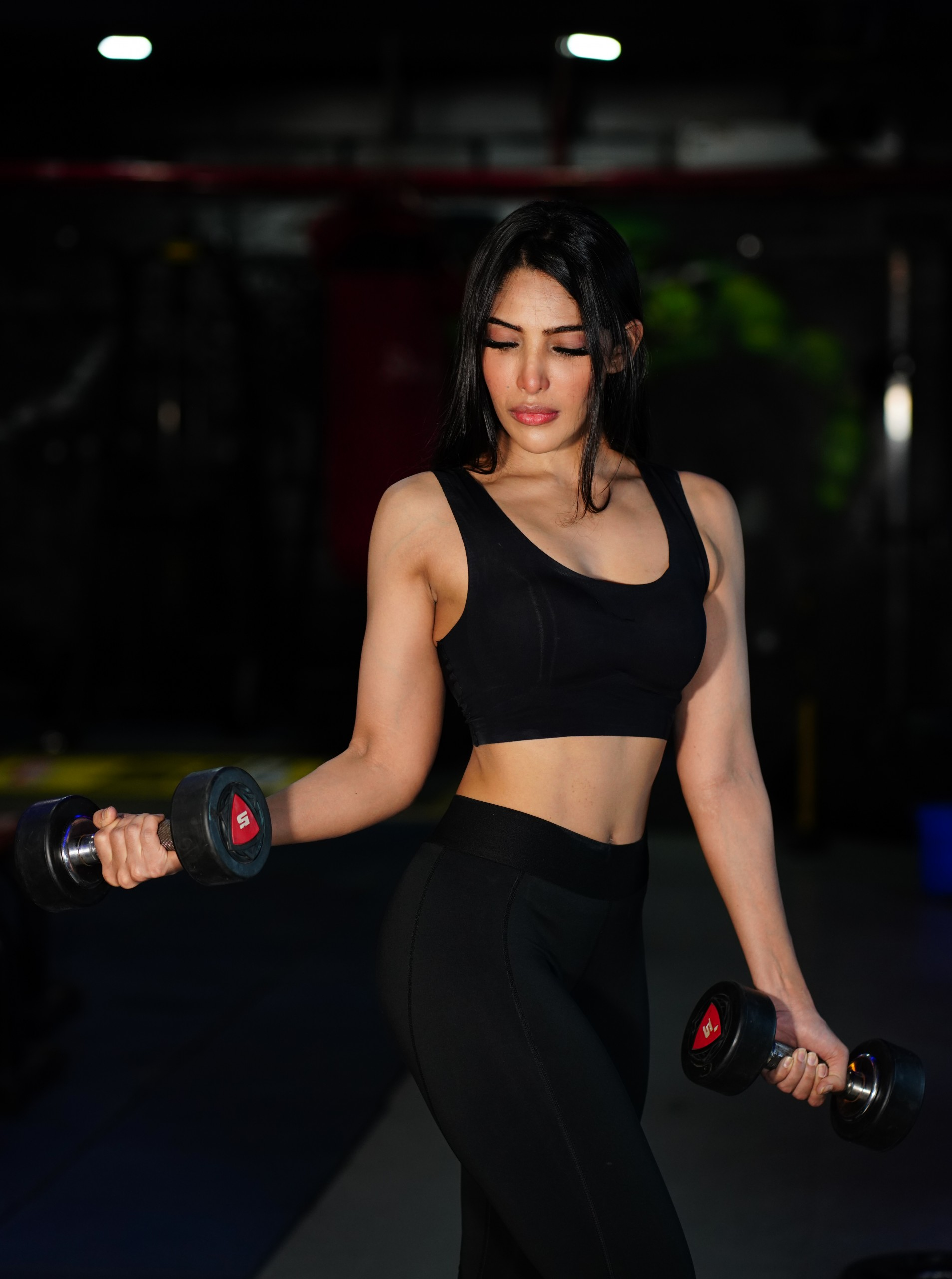 Sporty woman holding dumbbells in the gym