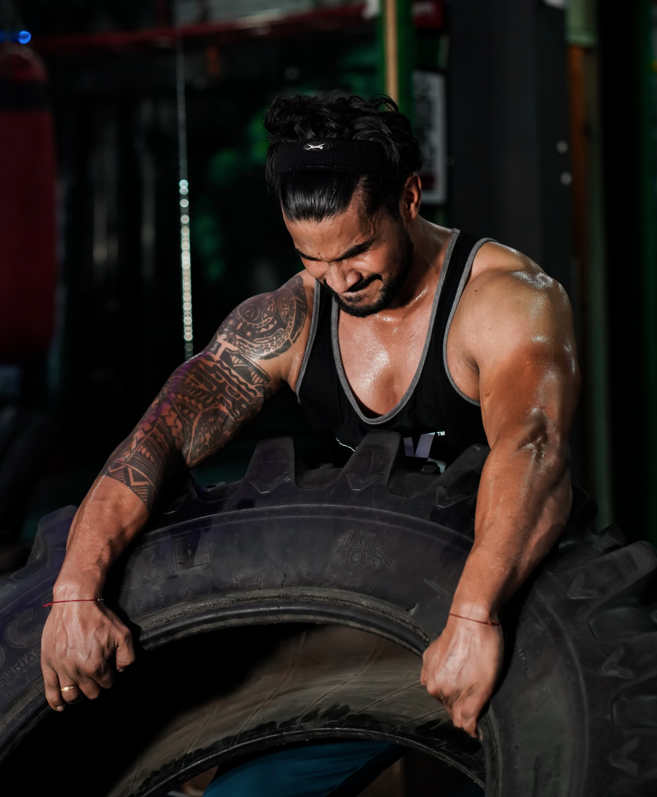 Strong man lifting Tractor tyre with arms
