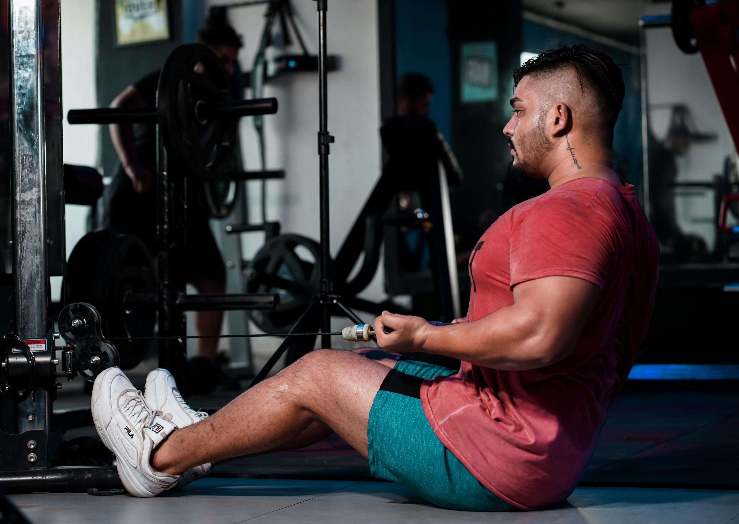 Strong muscles man pulling weights with arms in gym