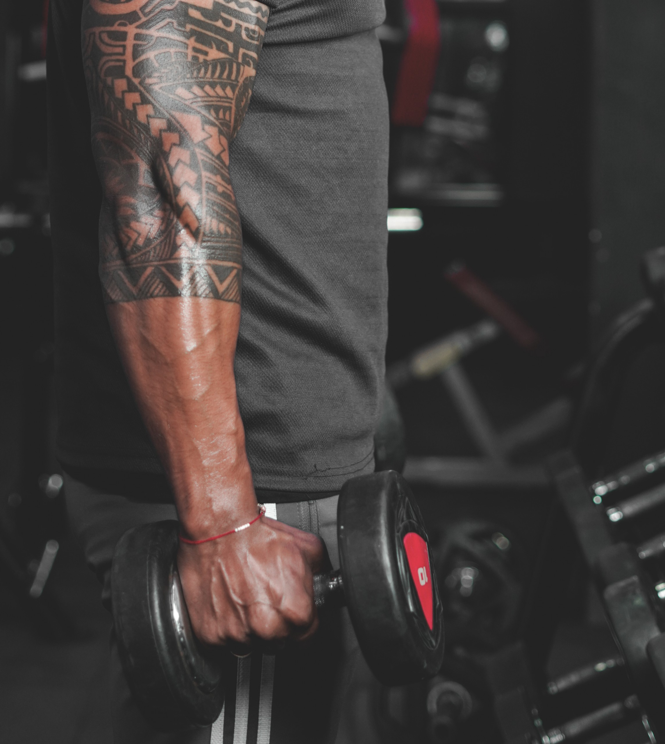 Tattooed Athlete lifting Dumbbells