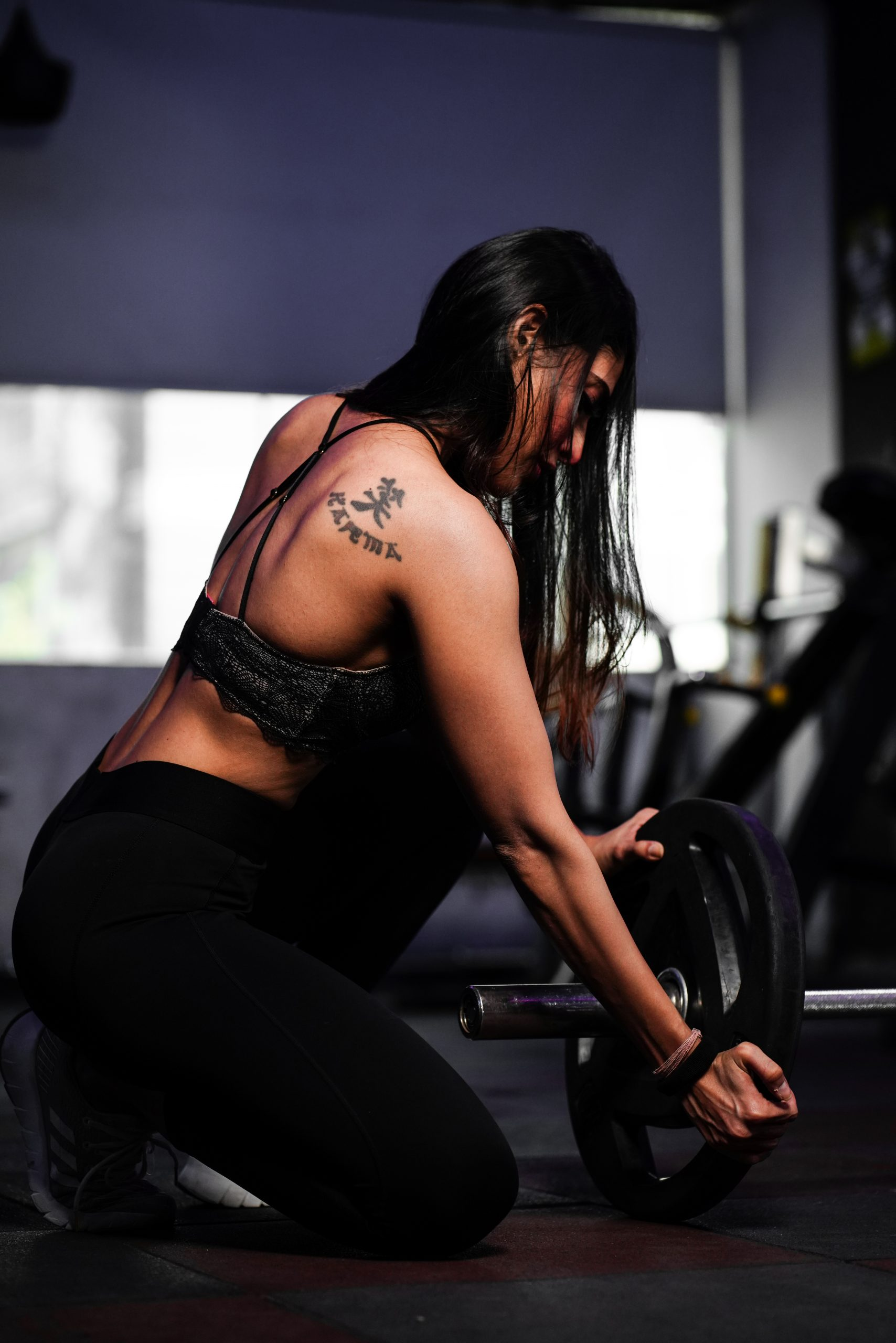 Tattooed Girl removing barbell wheel after exercise