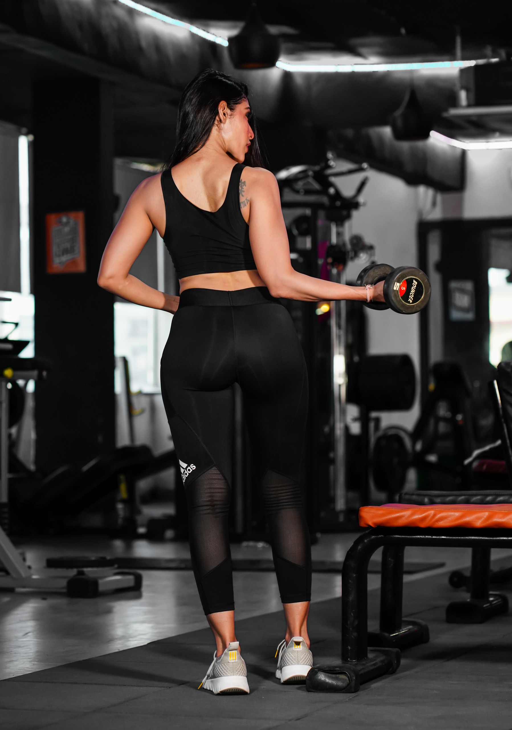 Woman back pose with dumbbells exercise