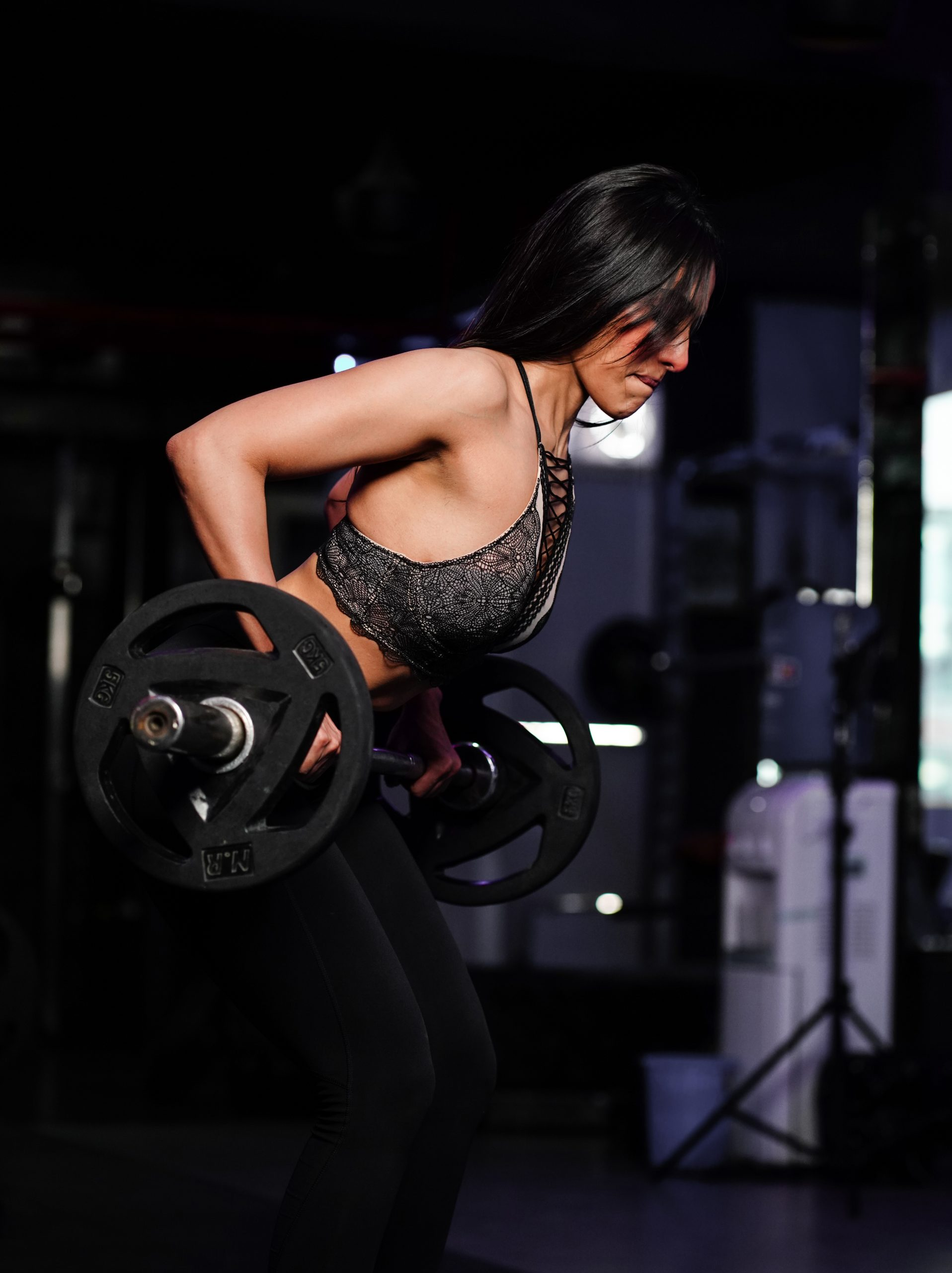 Young beautiful woman lifting weight barbell