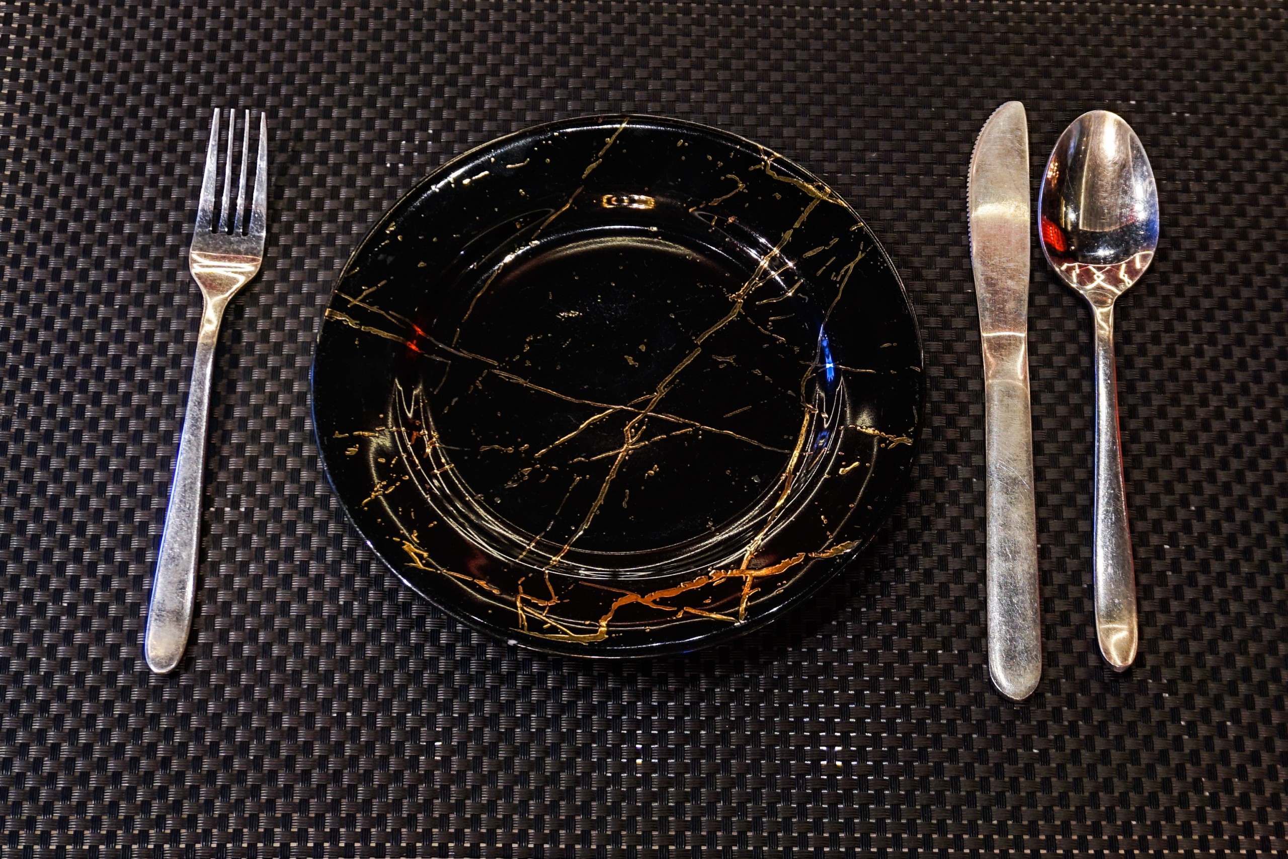 black plate and silverware on a table