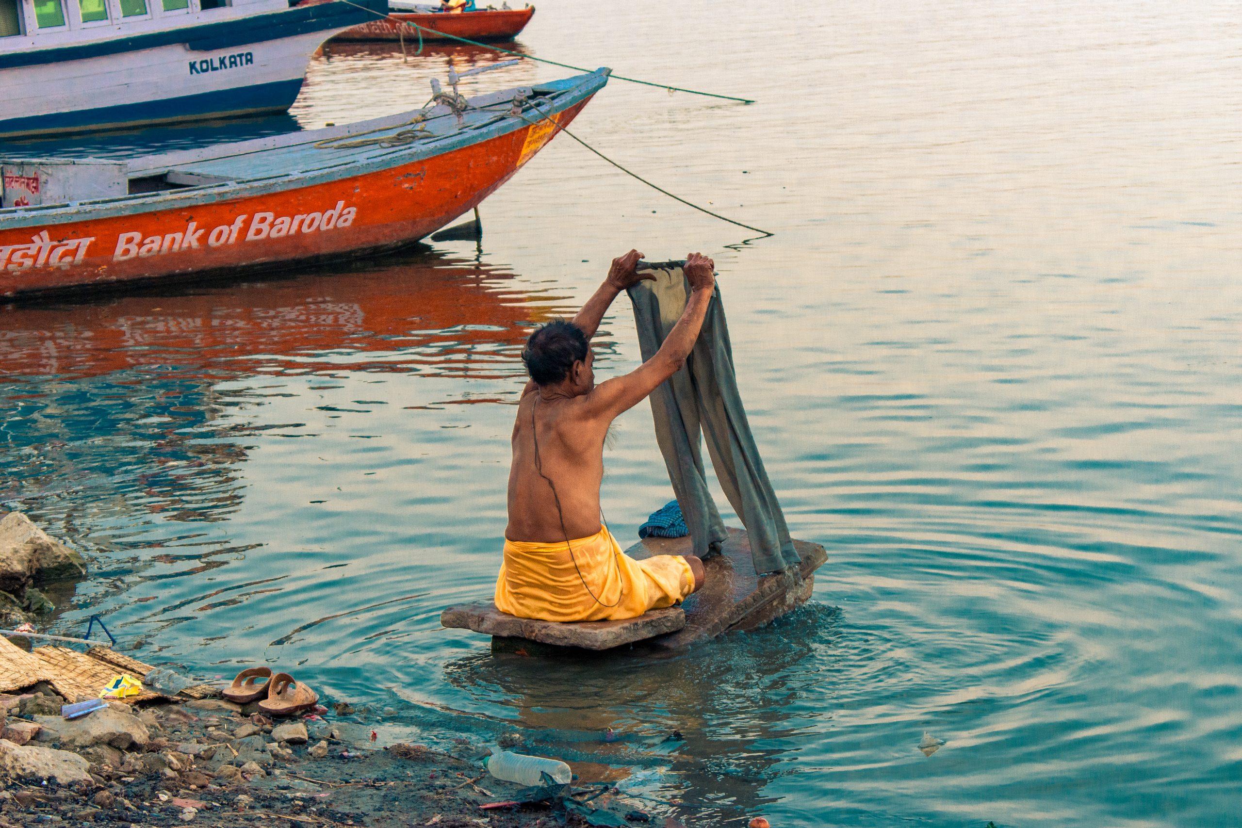 A man washing clothes in Ganga river.