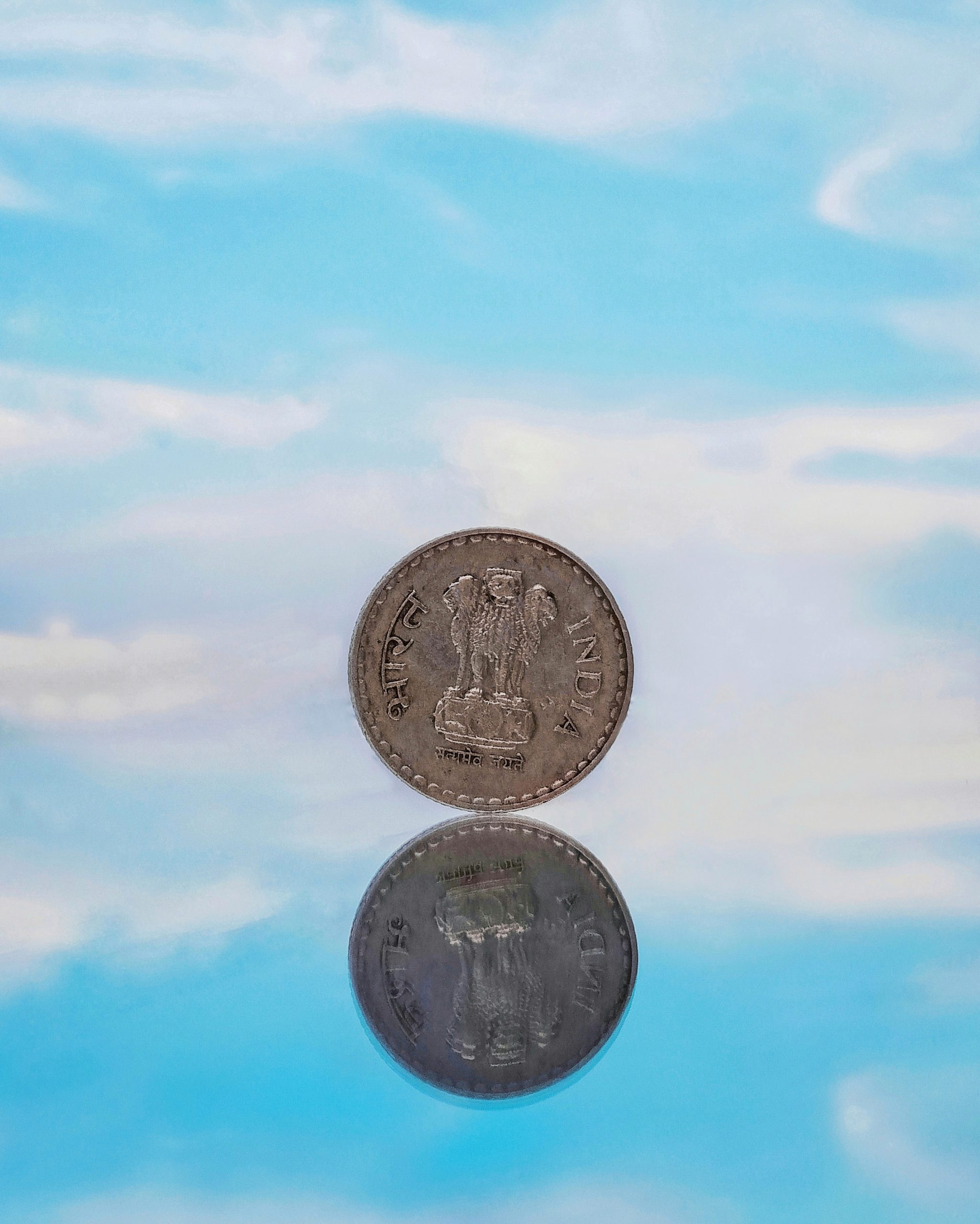 5 rupee coin with reflection and sky