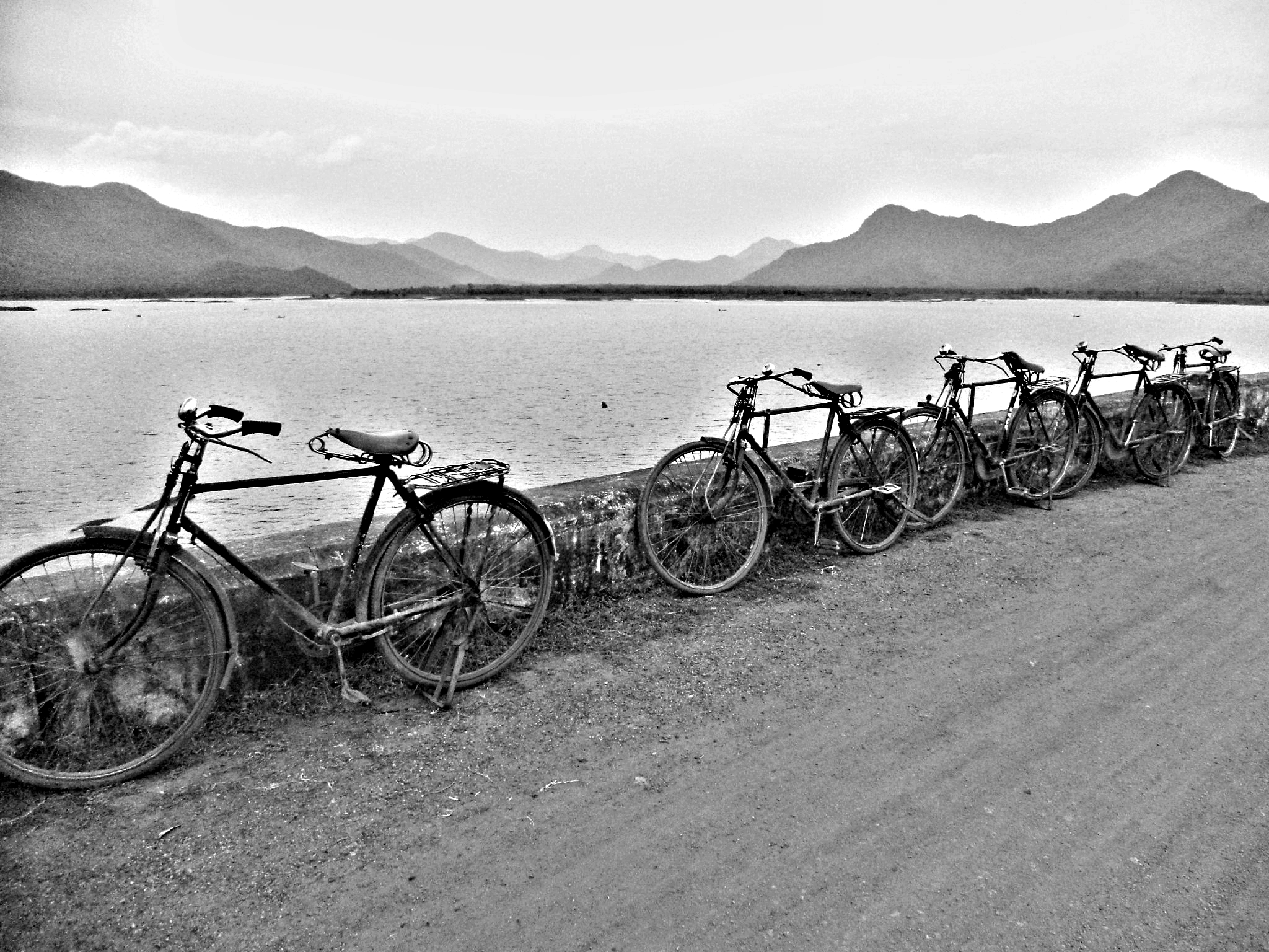 Cycles lined up beside a reservoir