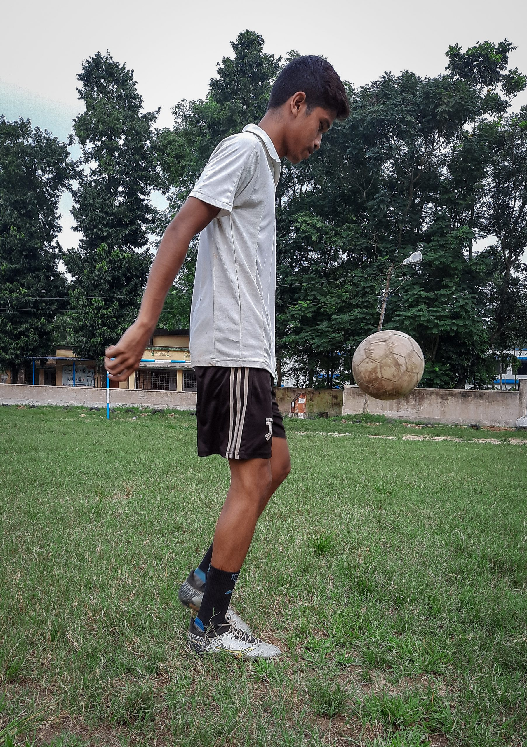 A boy juggling with football