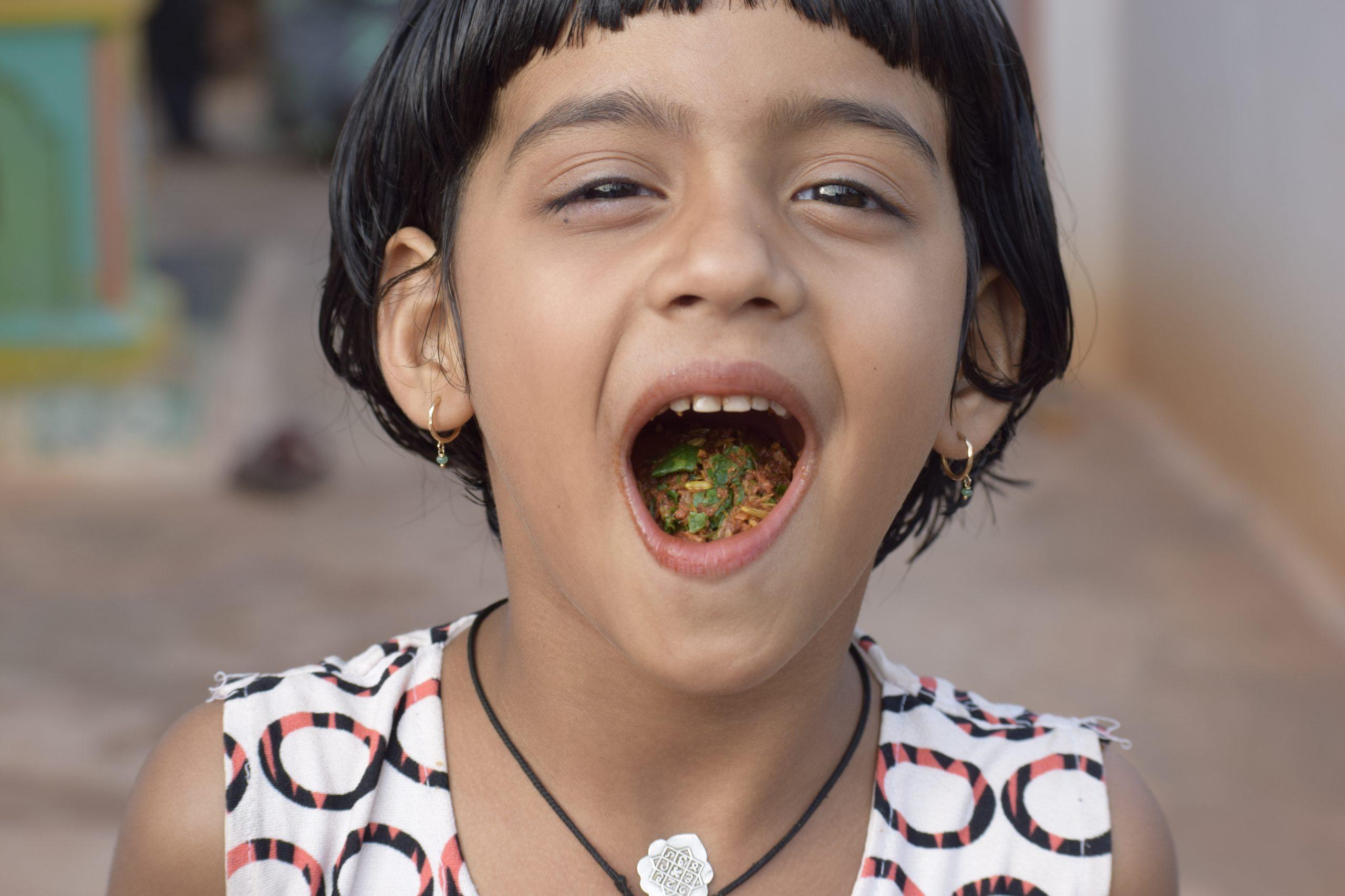 A girl child eating sweet pan