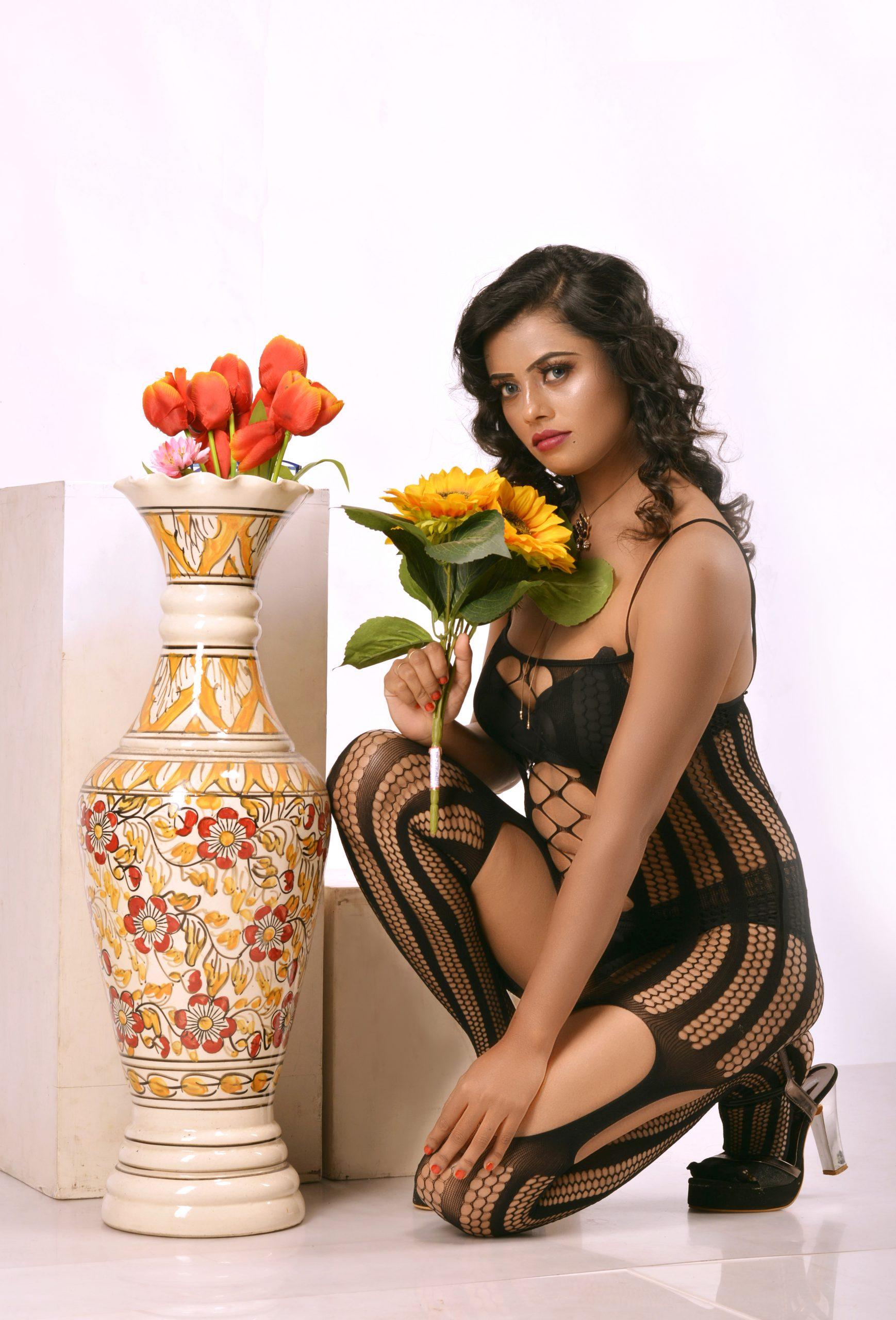 A girl posing near a flower pot