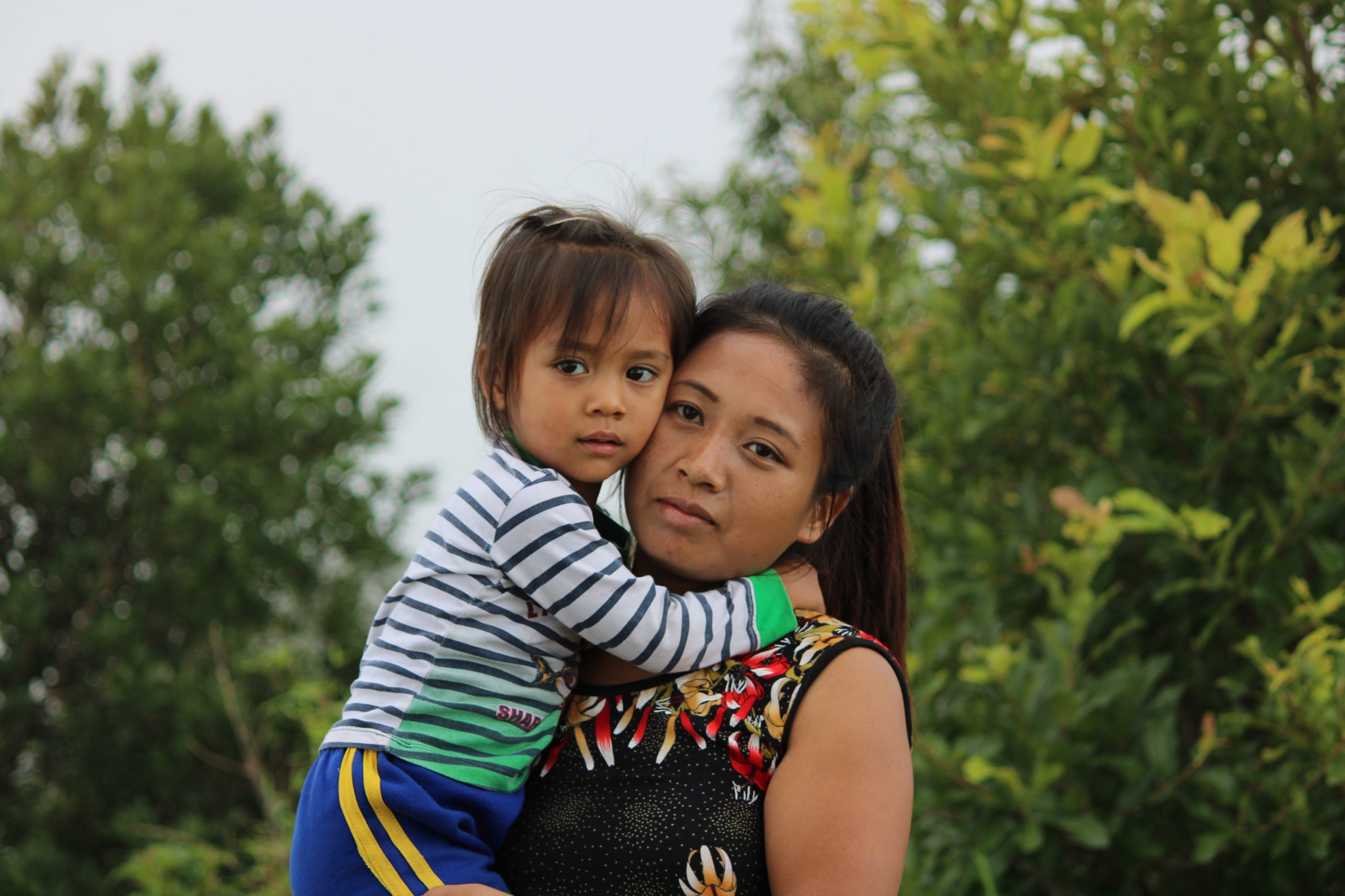 A woman with her daughter in her arms.