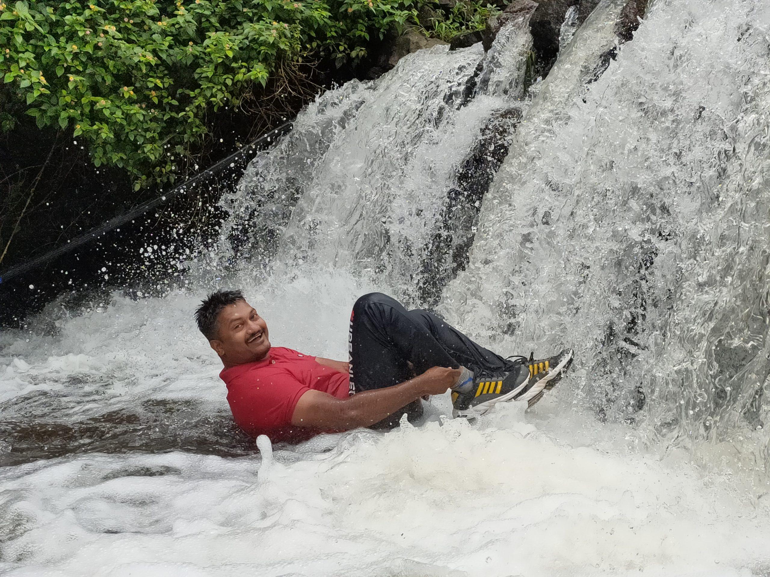 A man enjoying in a mini waterfall