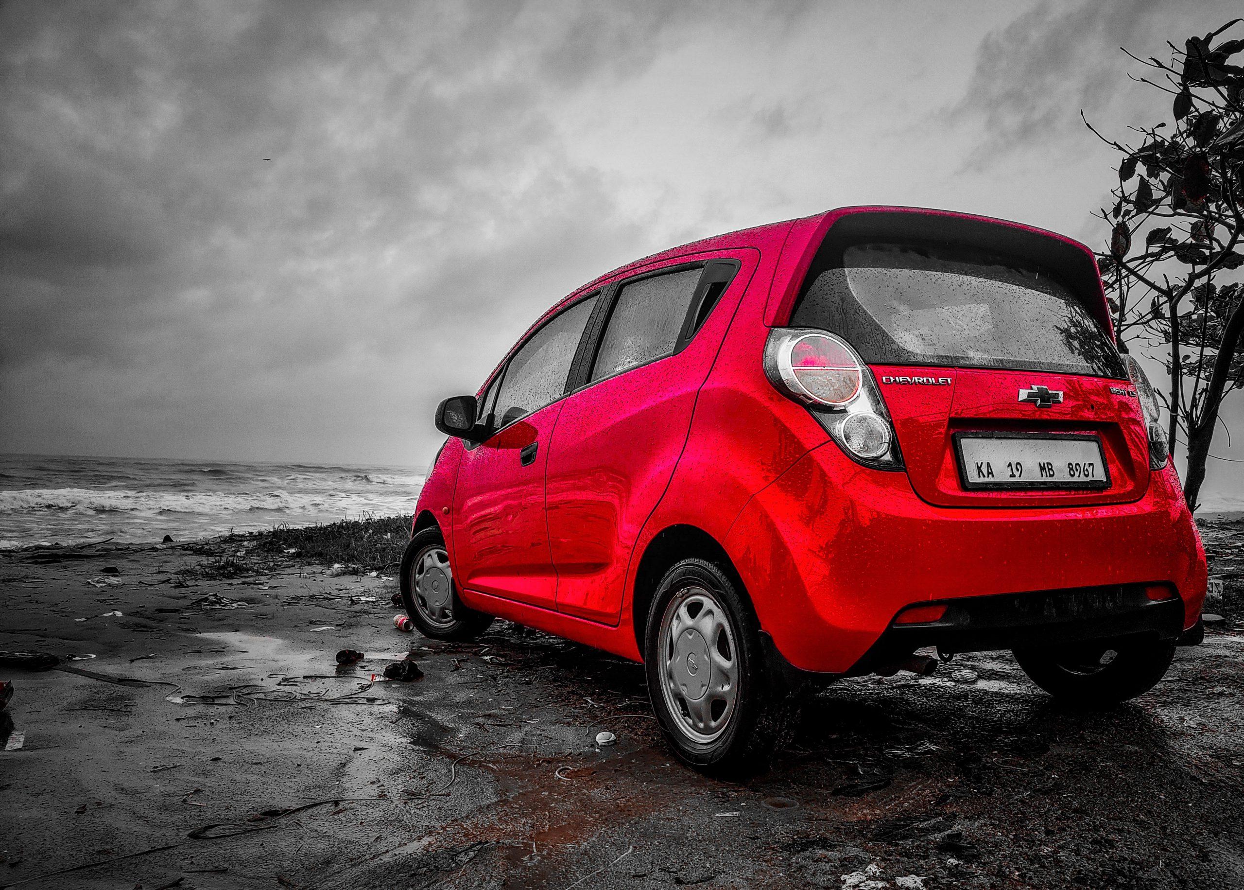 A red car beside a sea