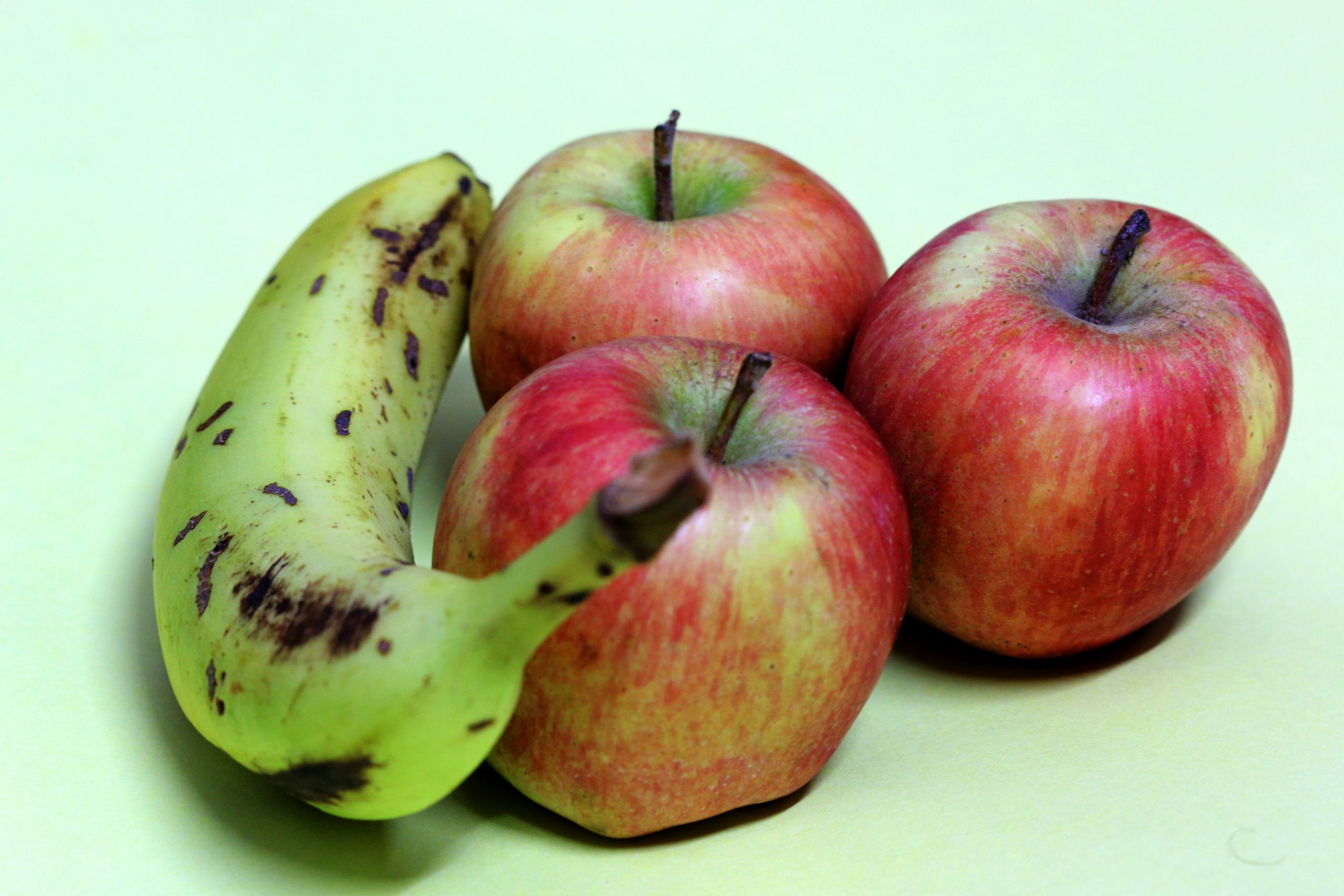 Apples and a banana on light green background.