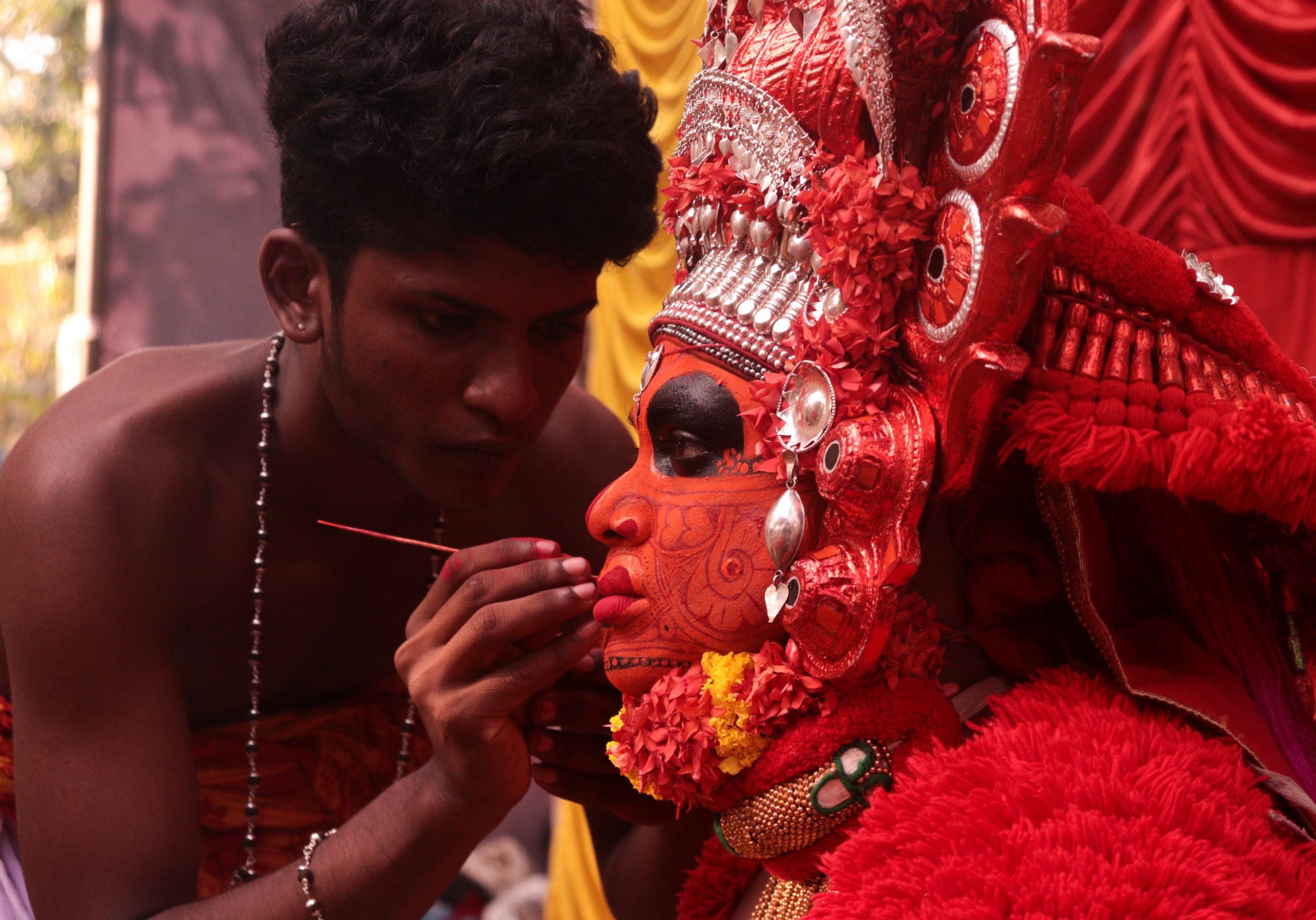 Artist painting face for Theyyam ritual