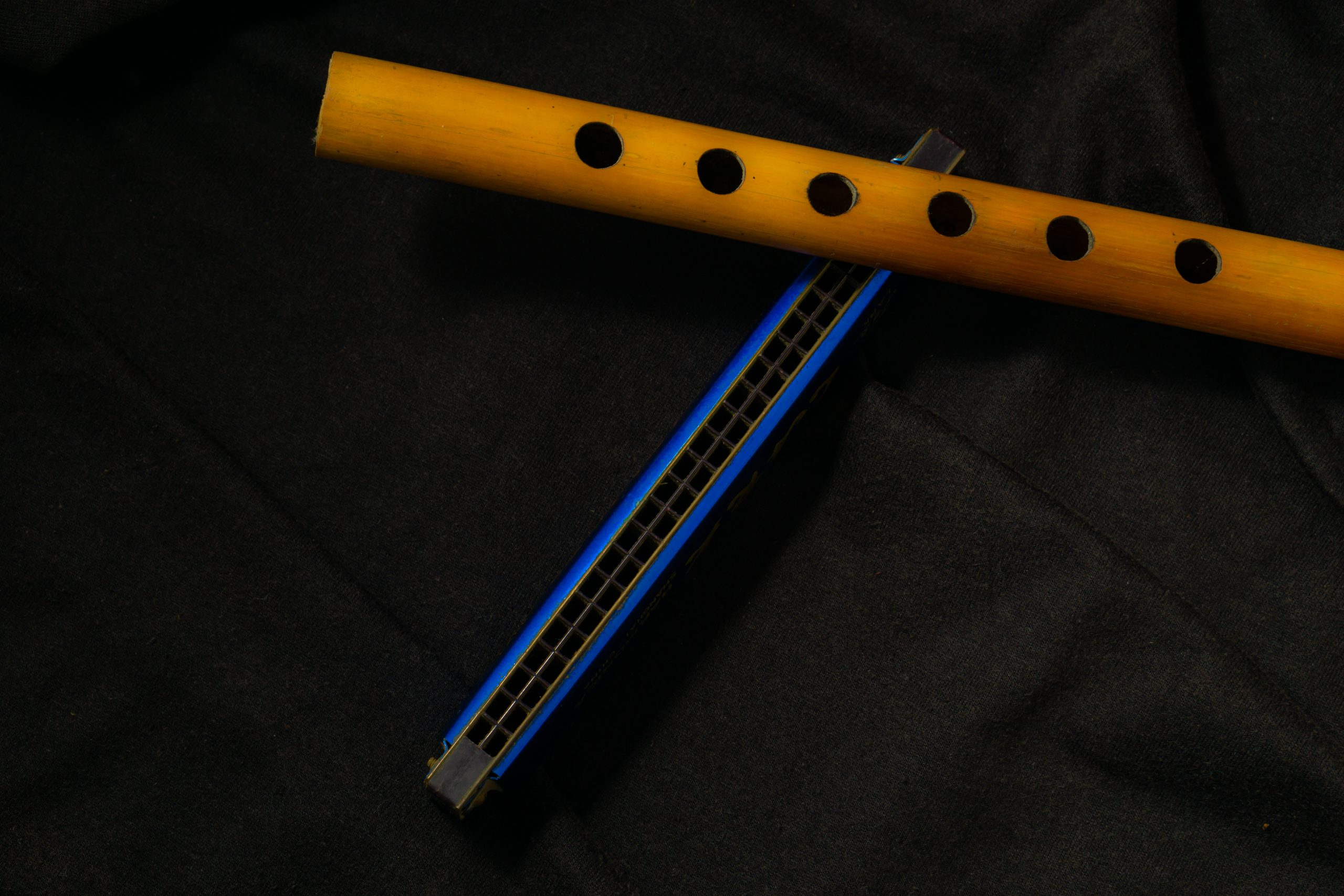 Bamboo flute and harmonica on a black background