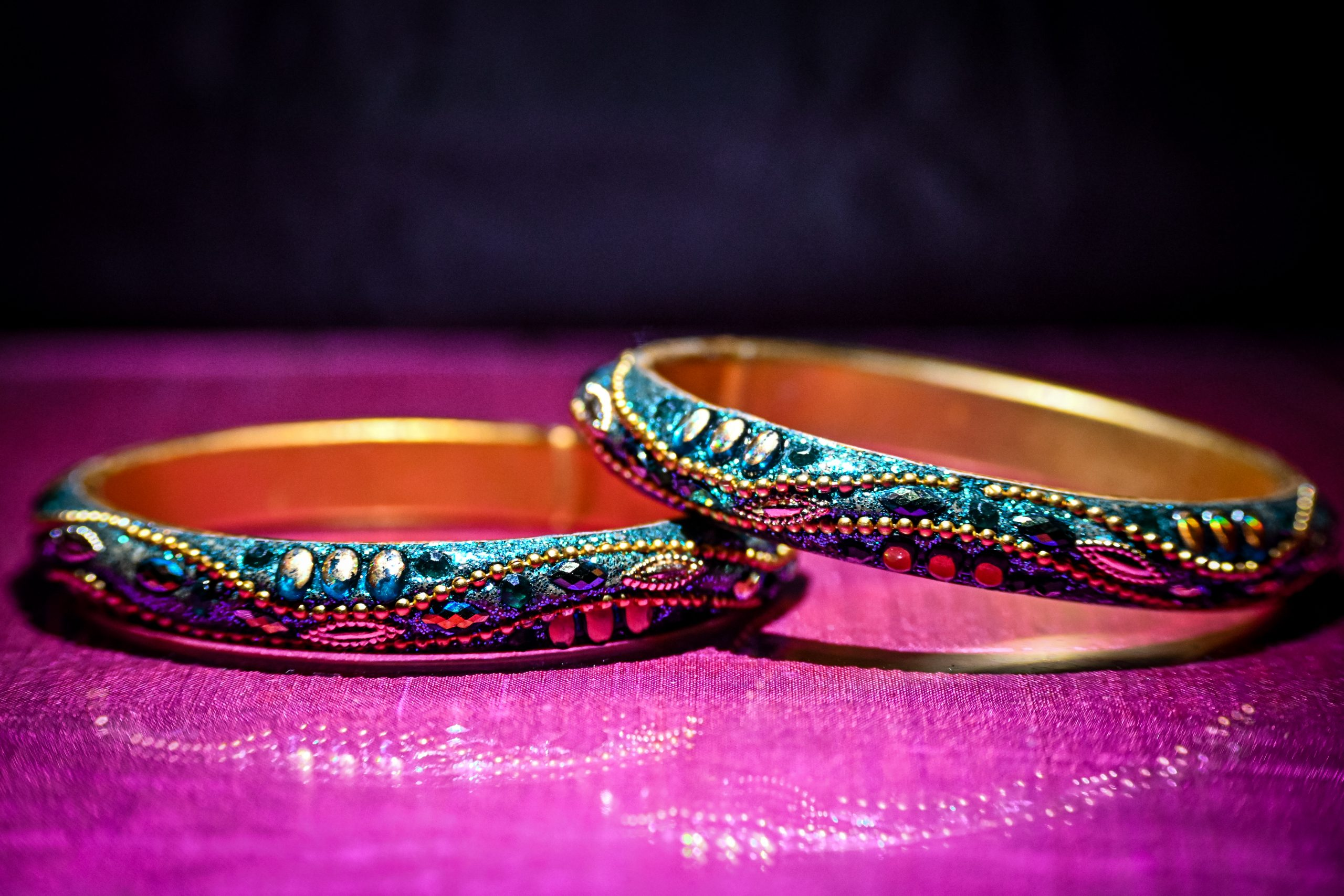A pair of woman bangles on purple background.